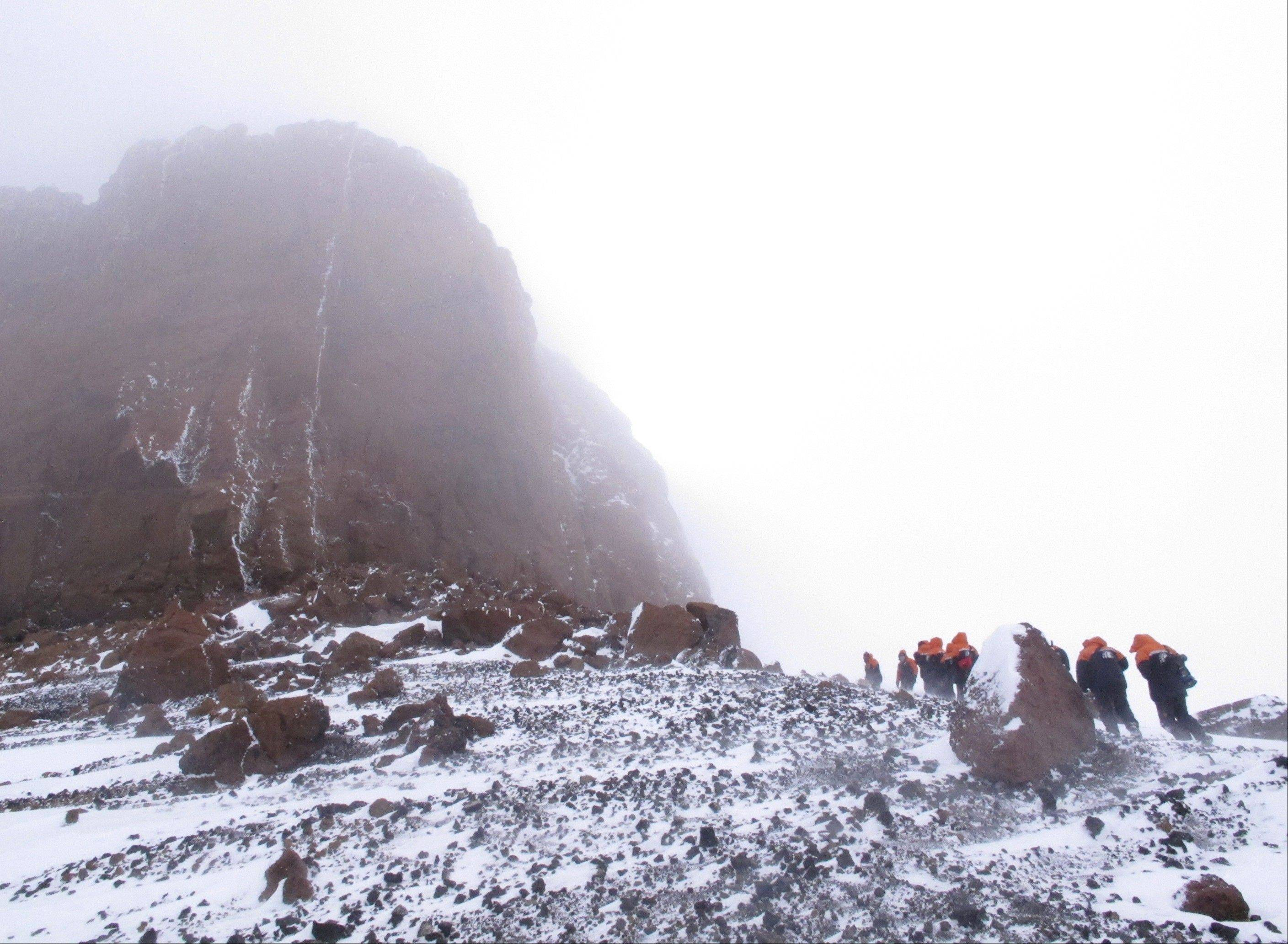 Tourists scale Crater Hill toward Castle Rock on Ross Island, Antarctica.