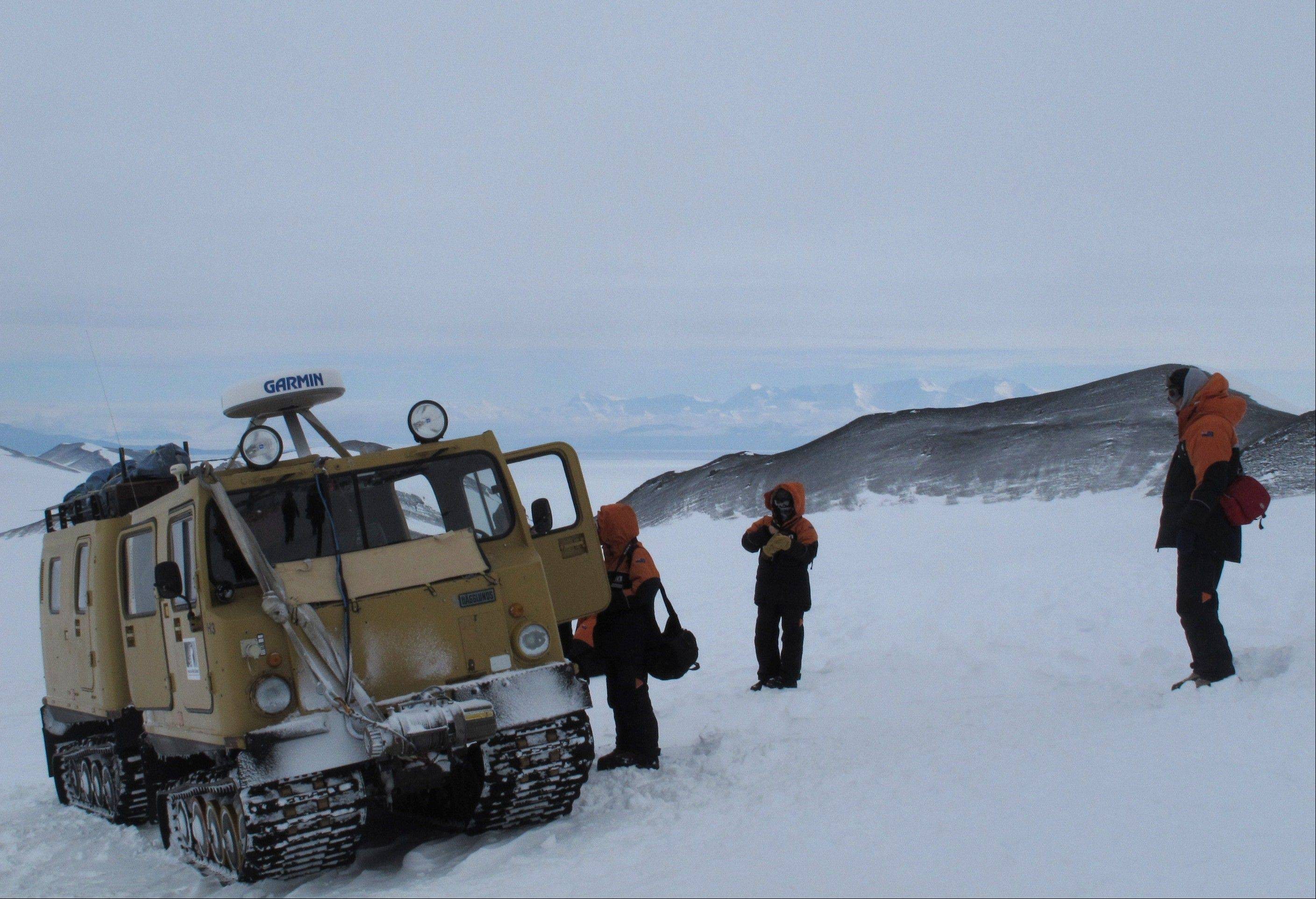Sightseers board an over-snow vehicle on Hut Point Peninsula of Ross Island in Antarctica.