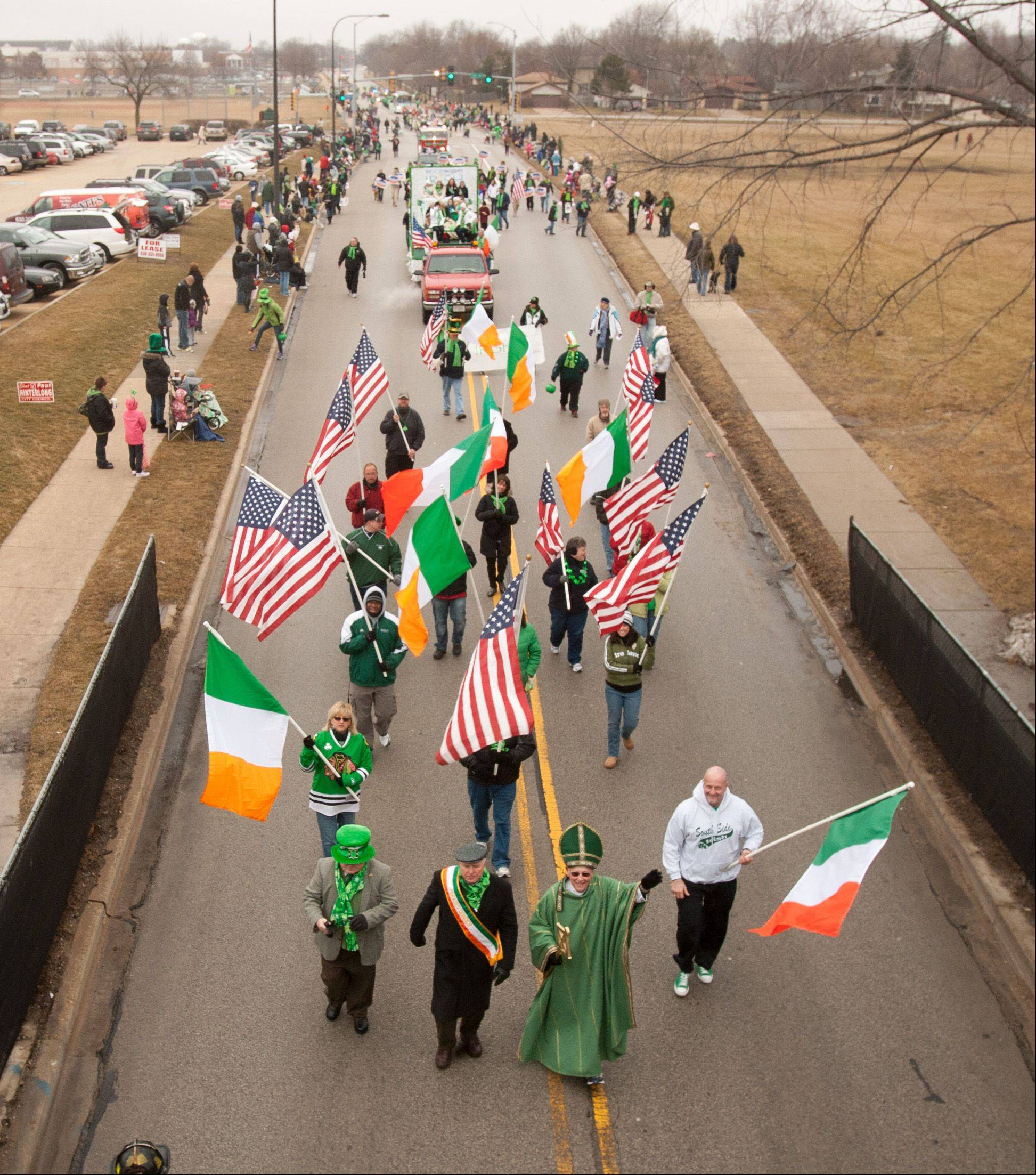 Bob Welsh of Crest Hill, dressed as St. Patrick, marches down Mill Street on Saturday near the beginning of the annual St. Patrick's Day Parade in Naperville.