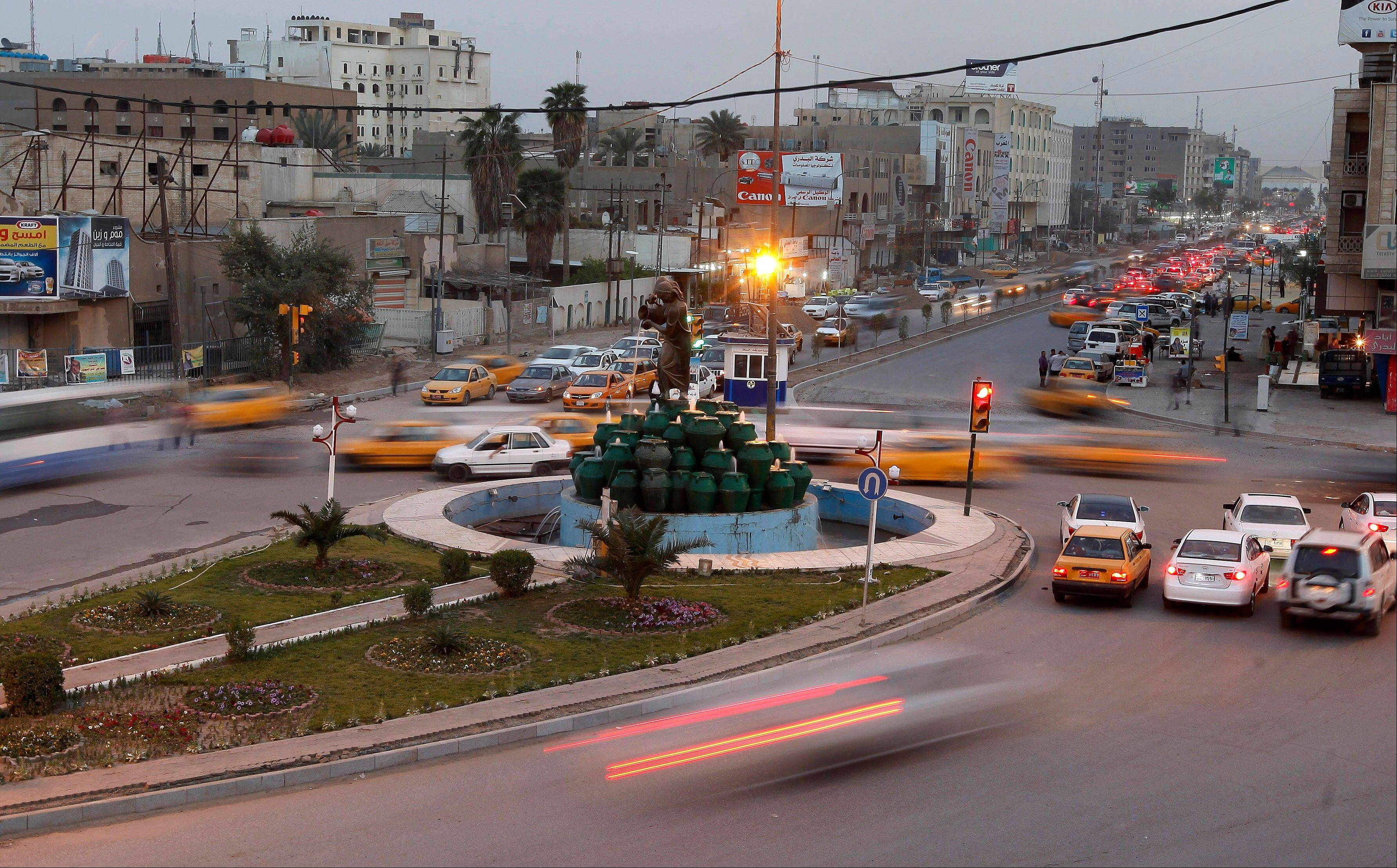 Cars drive through Kahramana Square Wednesday in Baghdad, Iraq.