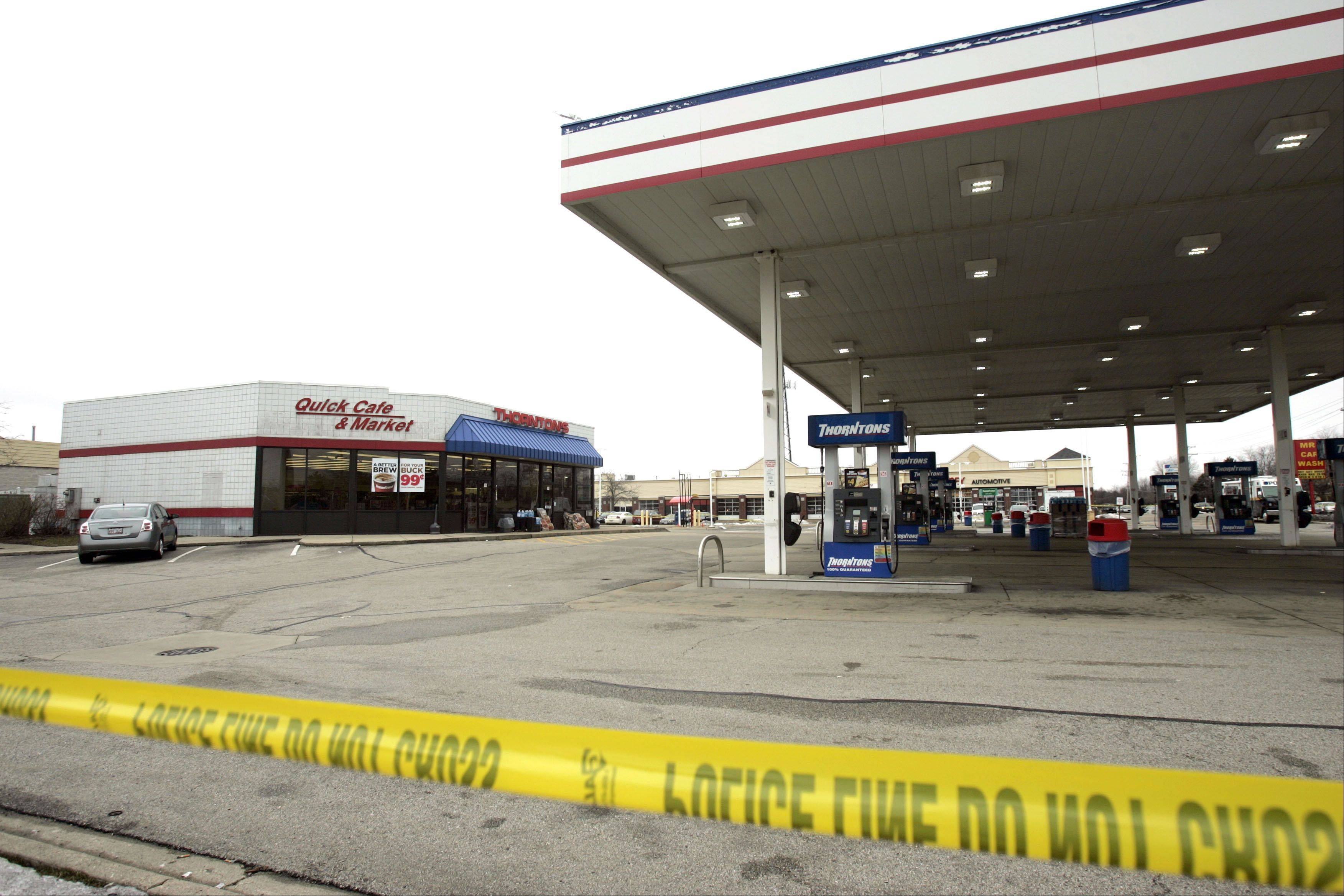 Police tape surrounds the Streamwood police as they work the scene where a gas station clerk was stabbed and killed early Saturday morning in Streamwood, police said.