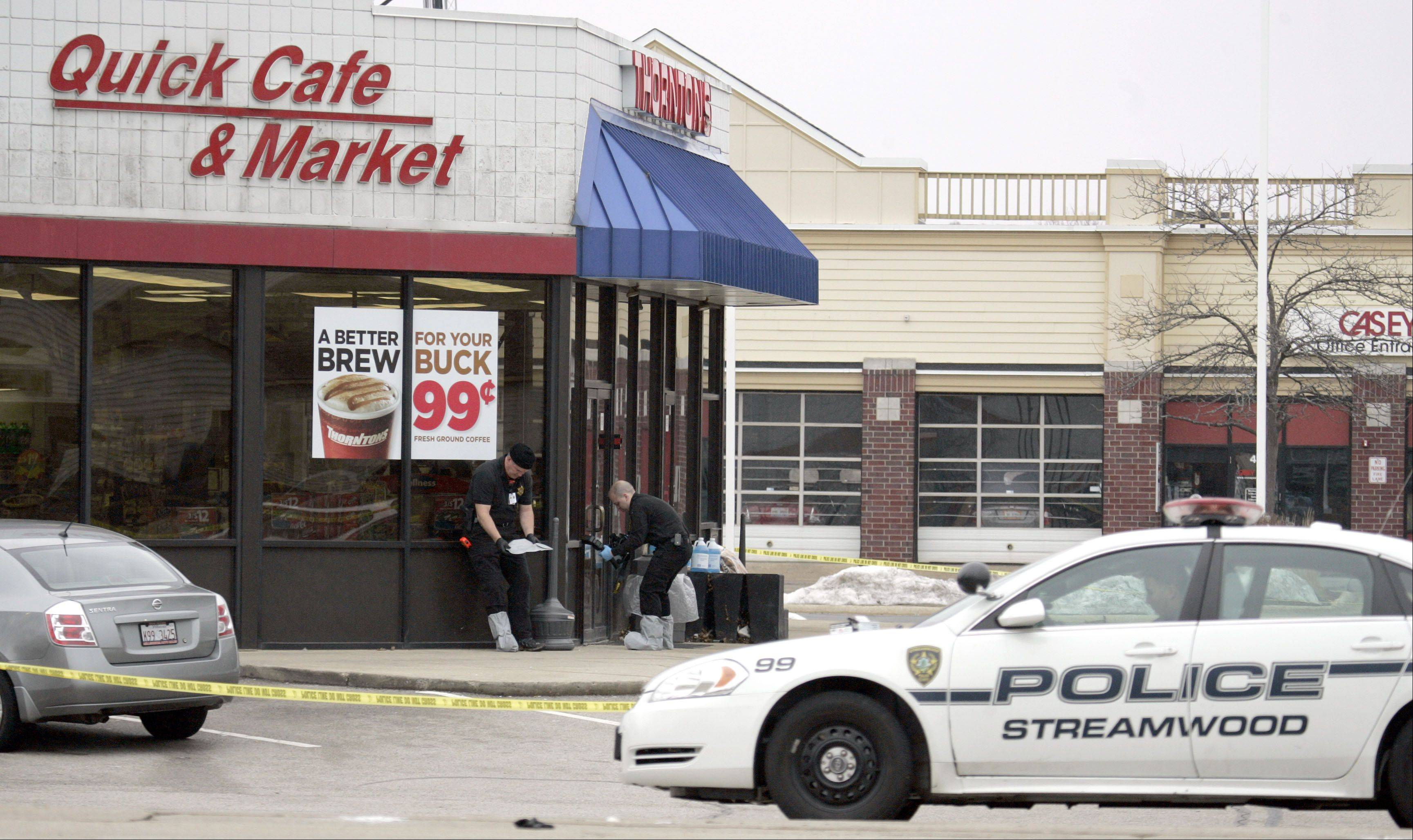 Two unidentified Streamwood police officers prepare to work the scene where a gas station clerk was stabbed and killed early Saturday morning in Streamwood, police said.