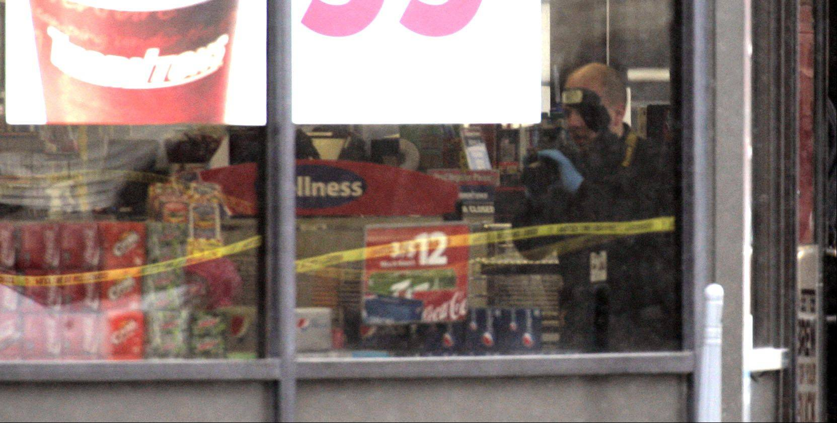 An unidentified Streamwood police photographer works the scene where police say a gas station clerk was stabbed and killed early Saturday morning in Streamwood.