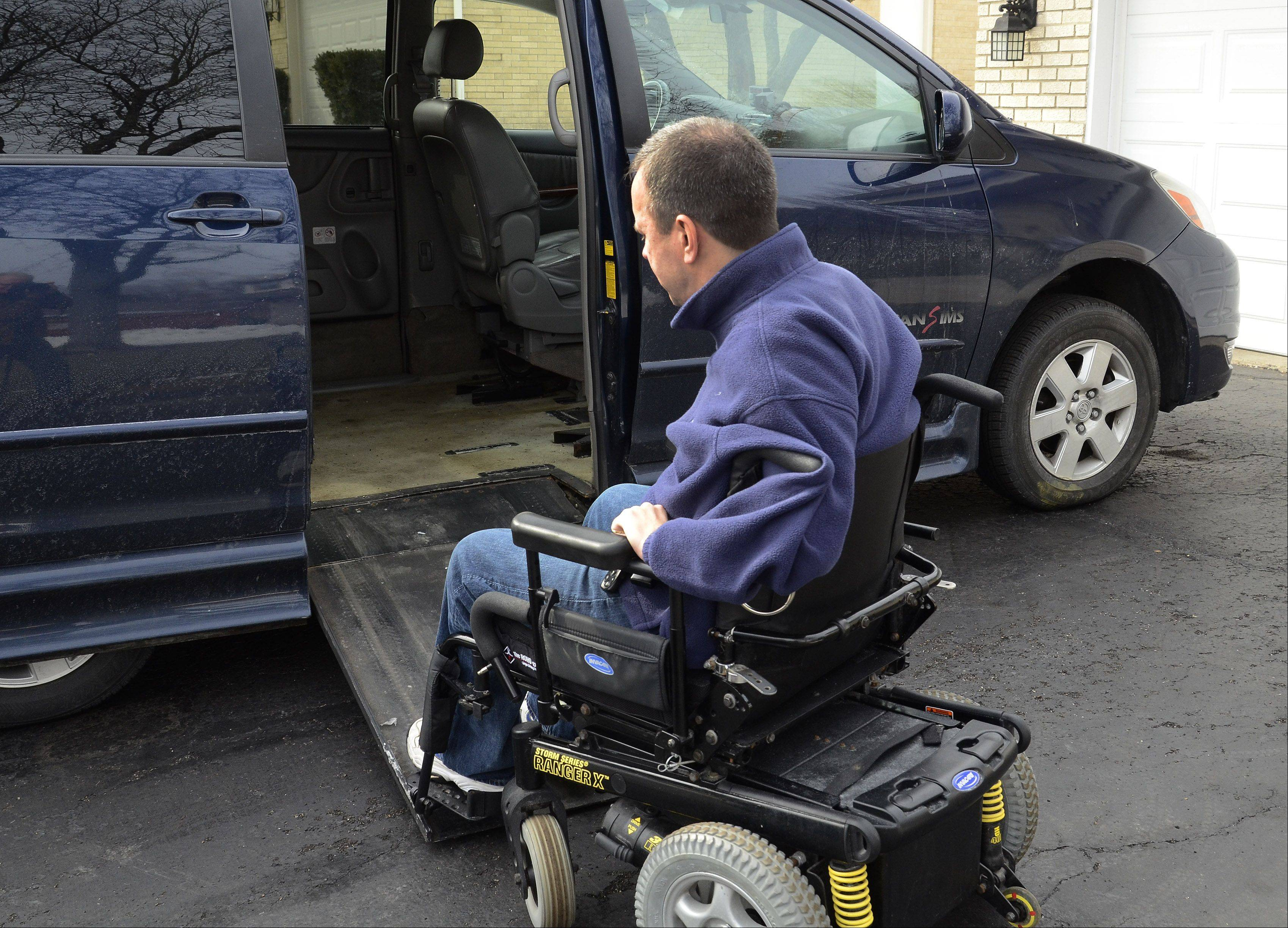 "Steve Herbst, National Mobility Awareness Month ""Local Hero"" contestant, demonstrates Friday how he gets in his handicap-accessible van."