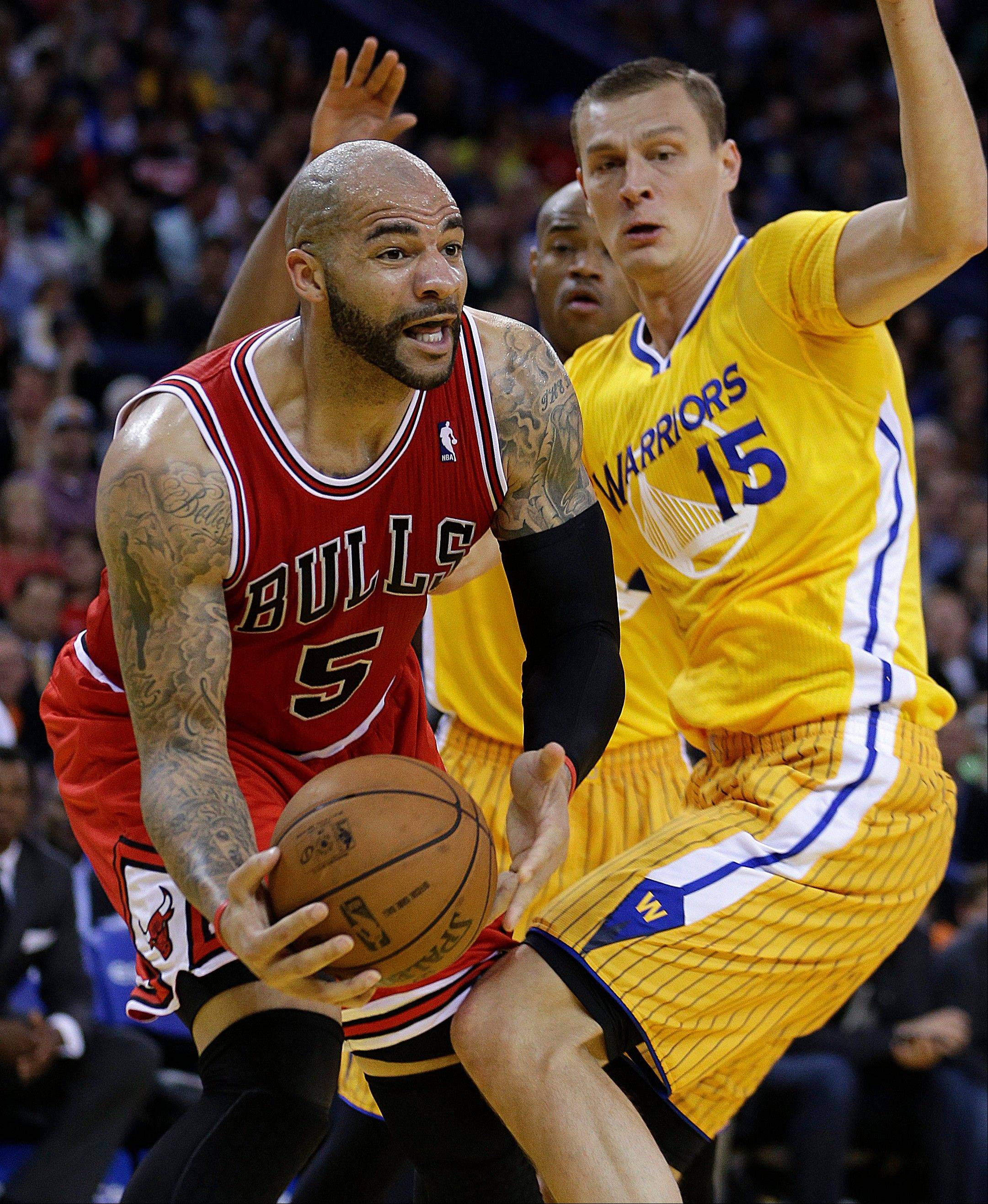 The Bulls� Carlos Boozer looks to pass around the Warriors� Andris Biedrins during Friday�s victory at Golden State.