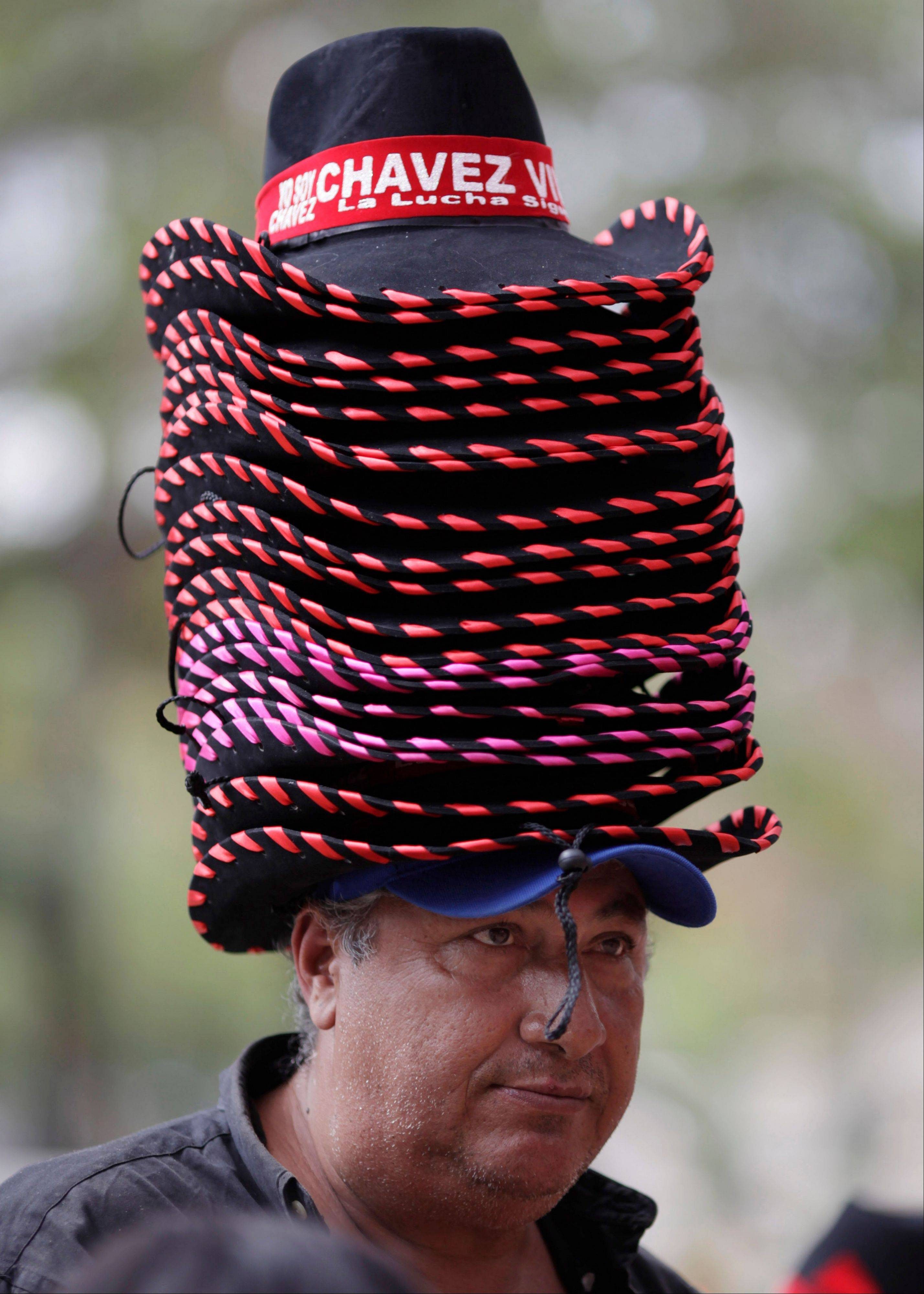 A vendor wears his merchandise of hats stacked high on his head Thursday outside the military academy where the body of the late President Hugo Chavez lies in state, in Caracas, Venezuela.