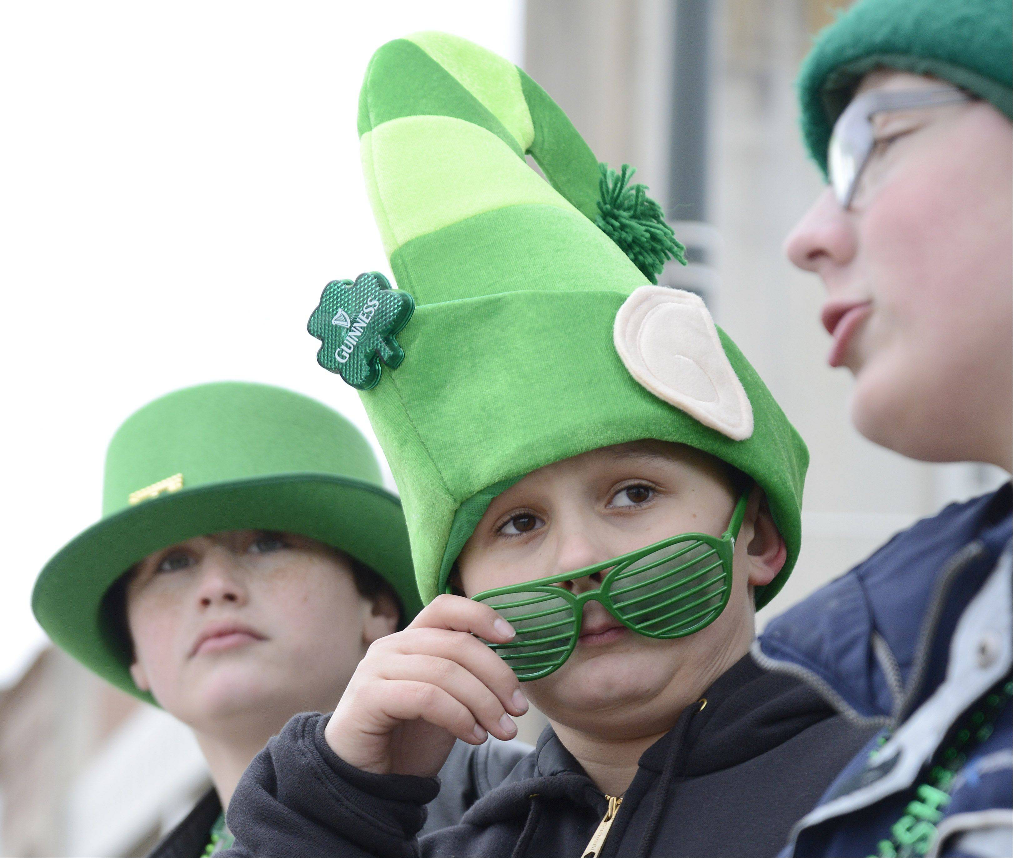 Joe Hanisch, 12, of St. Charles takes a peek at what's coming next in the St. Patrick's Day parade in St. Charles on Saturday. His birthday falls on St. Patrick's Day.