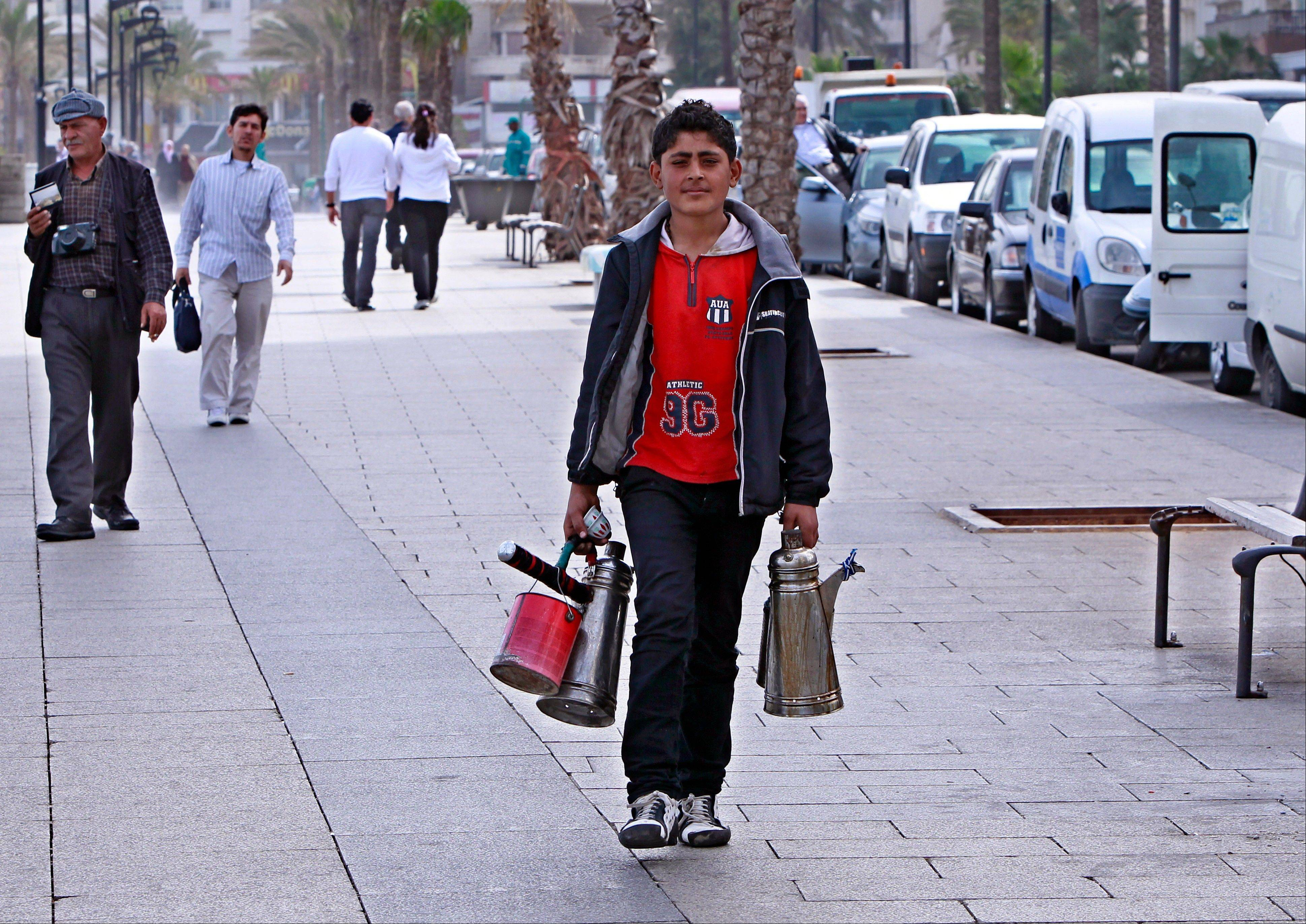 A Syrian boy Ayman, 14, who fled his home from Aleppo, makes a living by selling coffee in Beirut, Lebanon. Countless young Syrians are now frequently seen wandering the streets of Beirut, pumping gas at stations and sometimes begging for money.