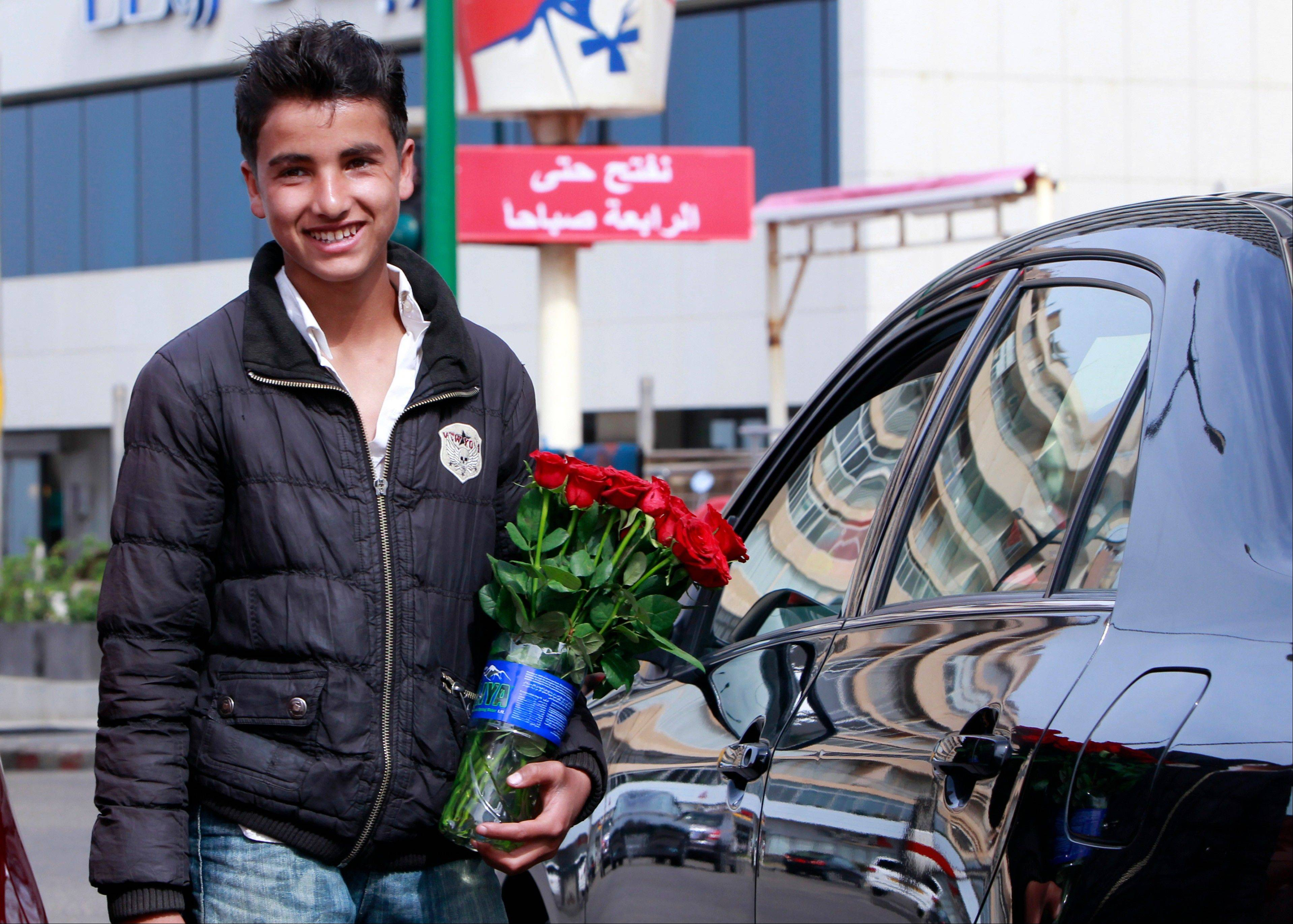 "A Syrian boy Aref, 15, who fled his home from Hassakeh, makes a living by selling flowers in Beirut, Lebanon. Save the Children, which is providing humanitarian and relief in Syria and neighboring countries, called on all groups taking part in the conflict to allow unfettered, safe access to populations in need and to ""ensure that everything is done to bring the fighting to an end."""
