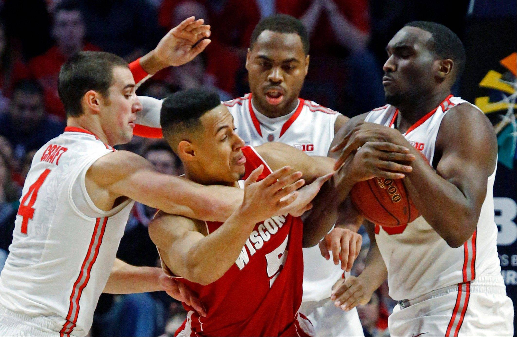 Ohio State forward Evan Ravenel, right, takes the ball away from Wisconsin's during the first half of the Buckeyes' win in the Big Ten tournament championship game Sunday. At left is guard Aaron Craft, and behind Evans is Deshaun Thomas.