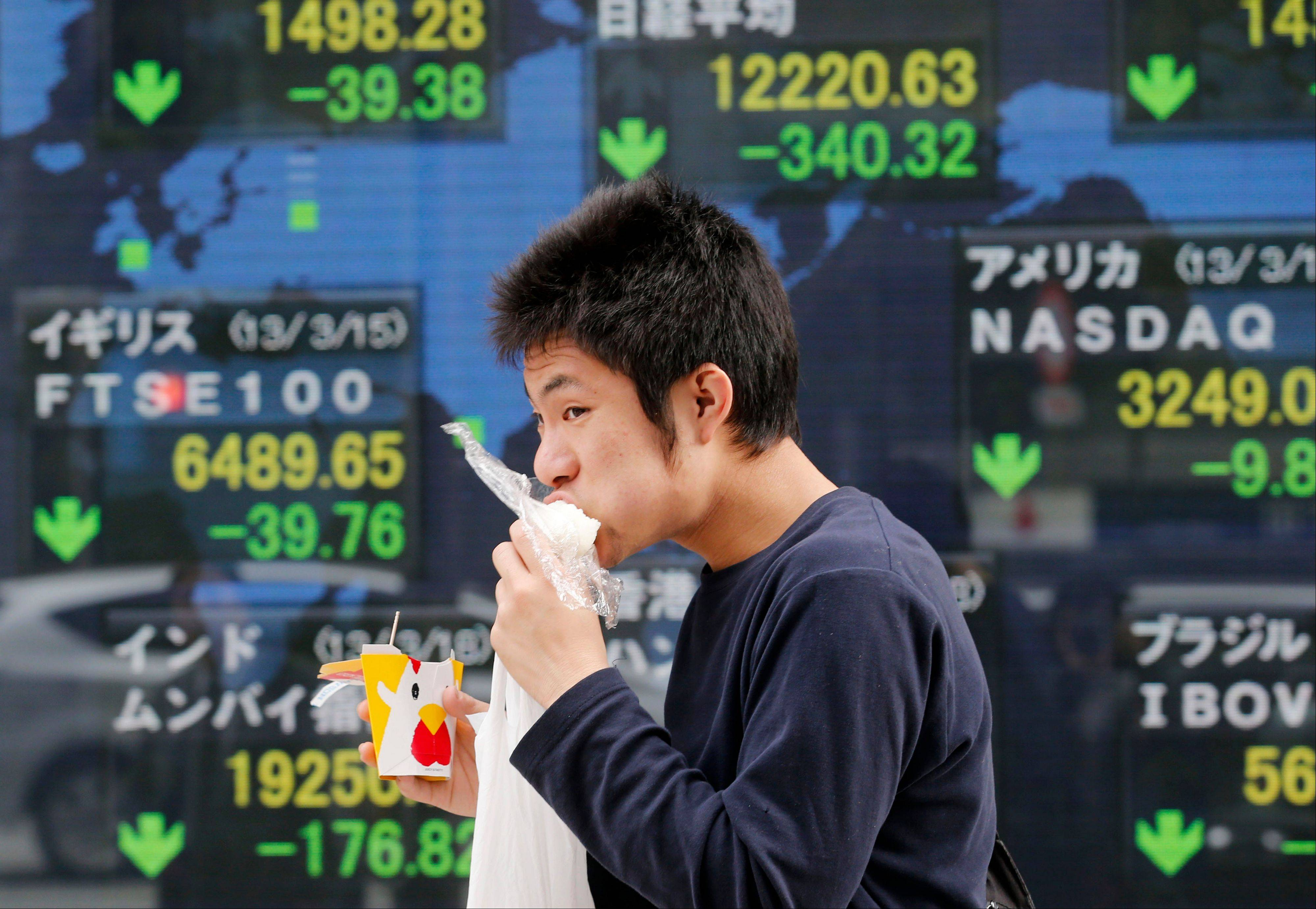 A man eats a rice ball while walking past an electronic stock board of a securities firm in Tokyo, Monday.