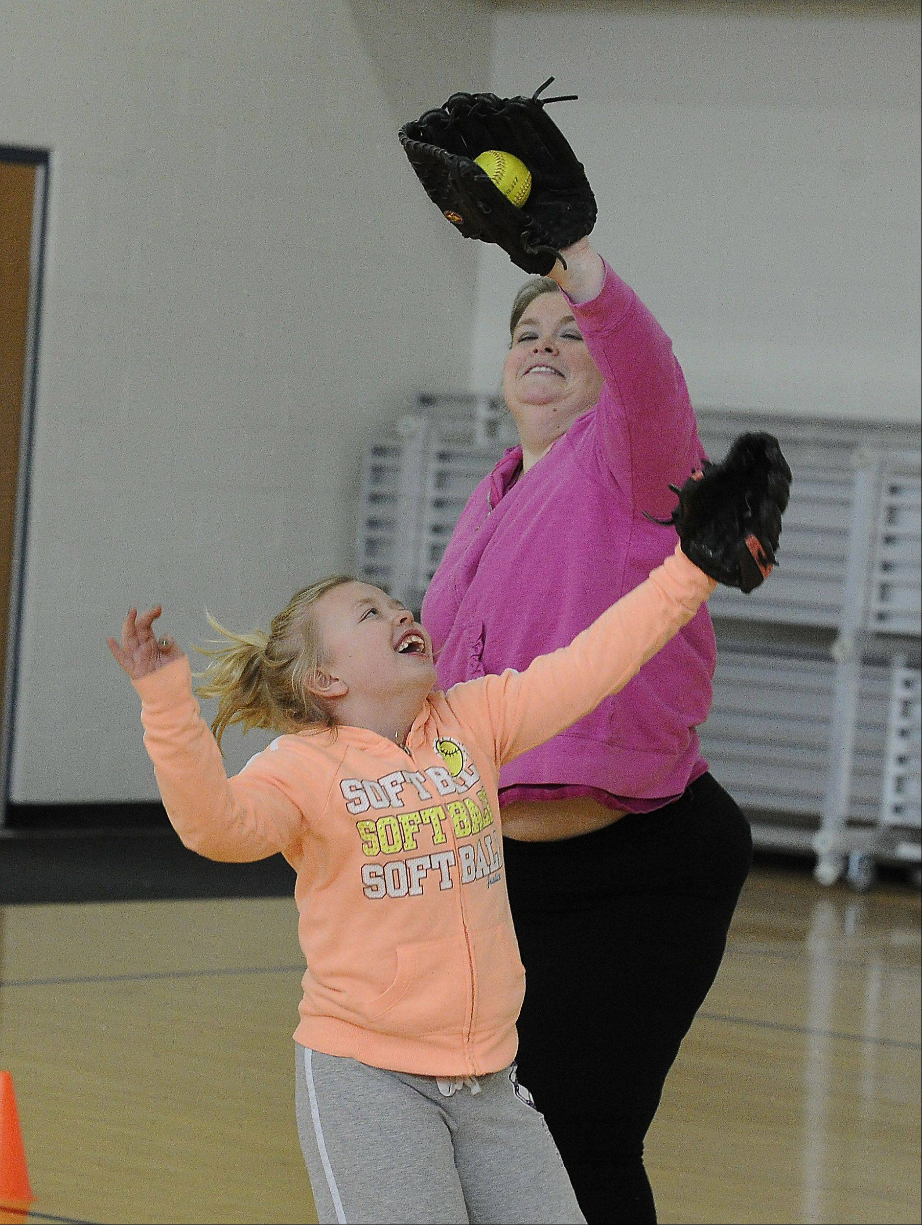 Megan McCarthy-Cook plays catch with her daughter Molly, 8, in the gym at the Hoffman Estates Park District as part of her exercise routine.