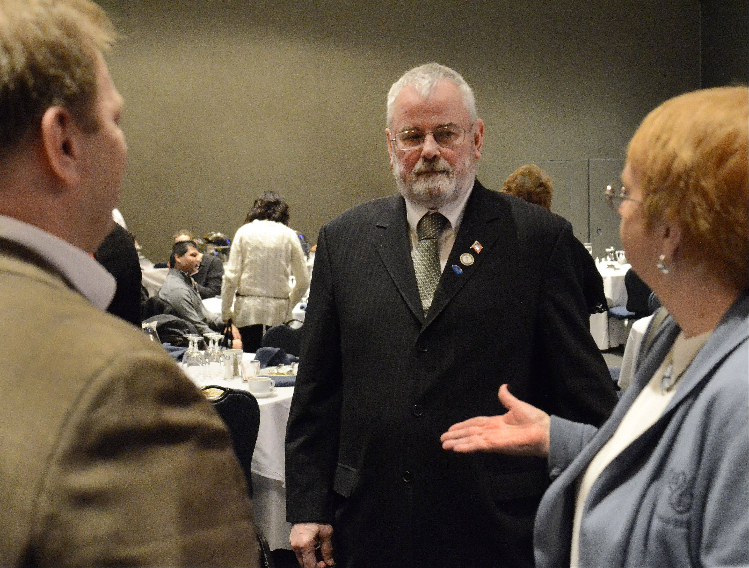 Hoffman Estates Mayor William McLeod talks with village Trustees Gary Pilafas and Karen Mills after giving his State of the Village address Monday.