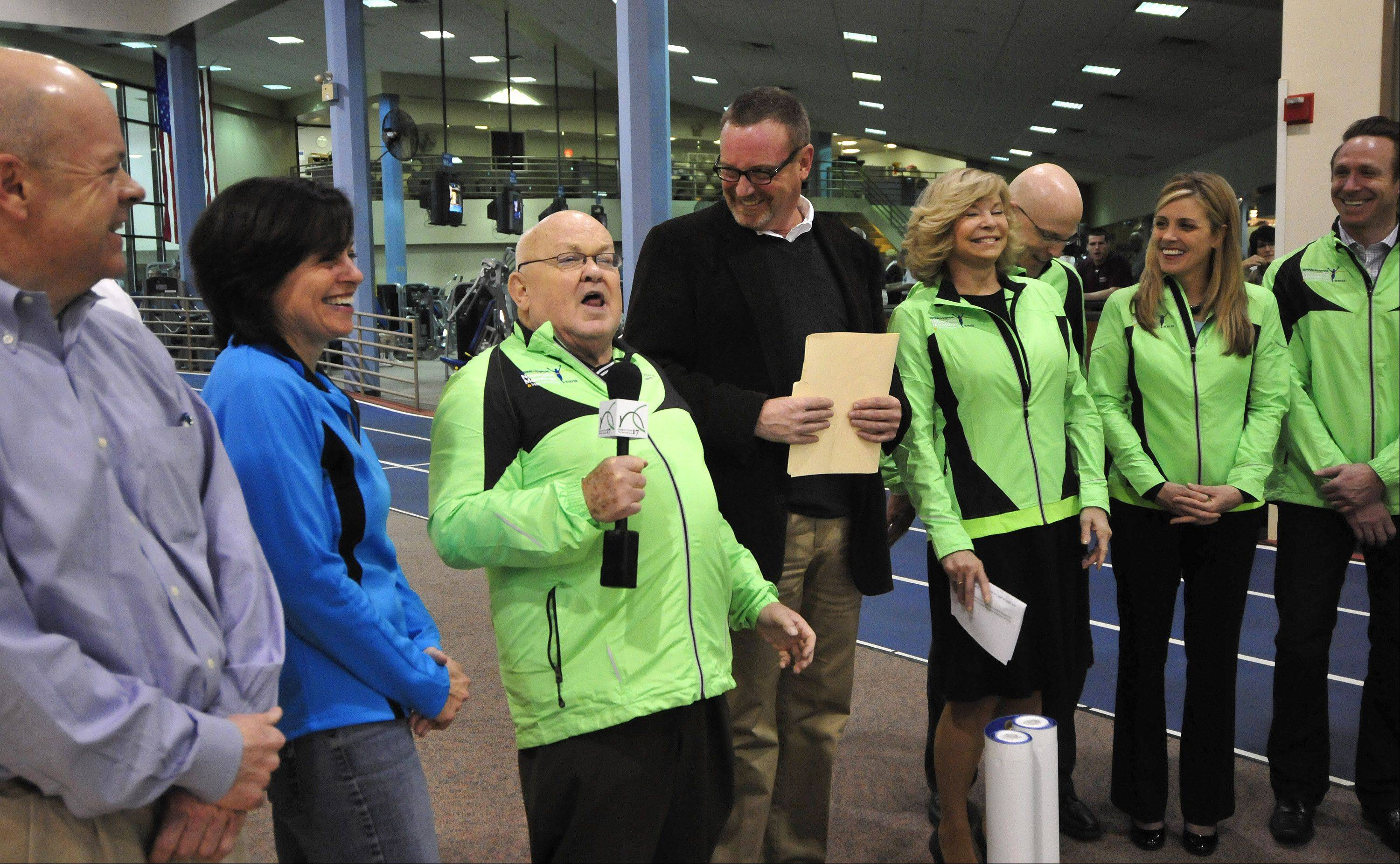 Officials from Edward Hospital in Naperville were joined by Mayor George Pradel, third from left, as he fired up the crowd Monday to unveil the starting banner for Naperville's inaugural marathon this fall. The event was held on the running track at the Edward Health & Fitness Center, next to the hospital.