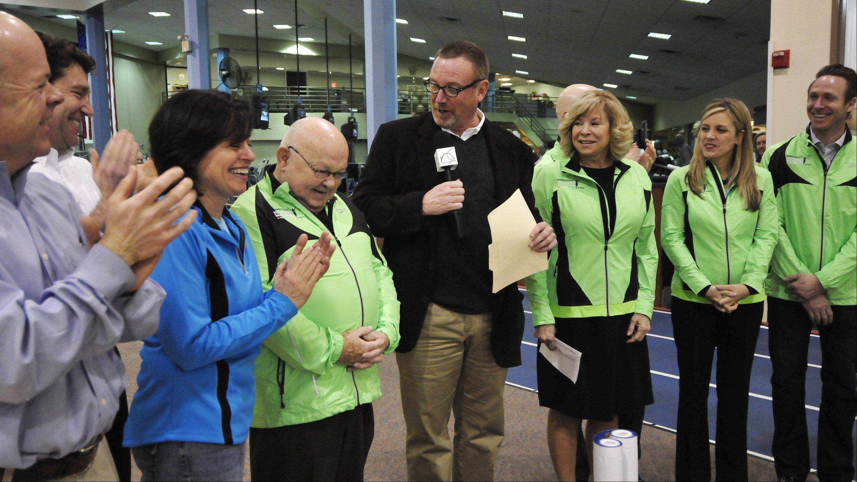 Naperville Mayor George Pradel, third from left, acknowledges the applause after he fired up the crowd with a rousing invitation to run in the city's inaugural marathon.