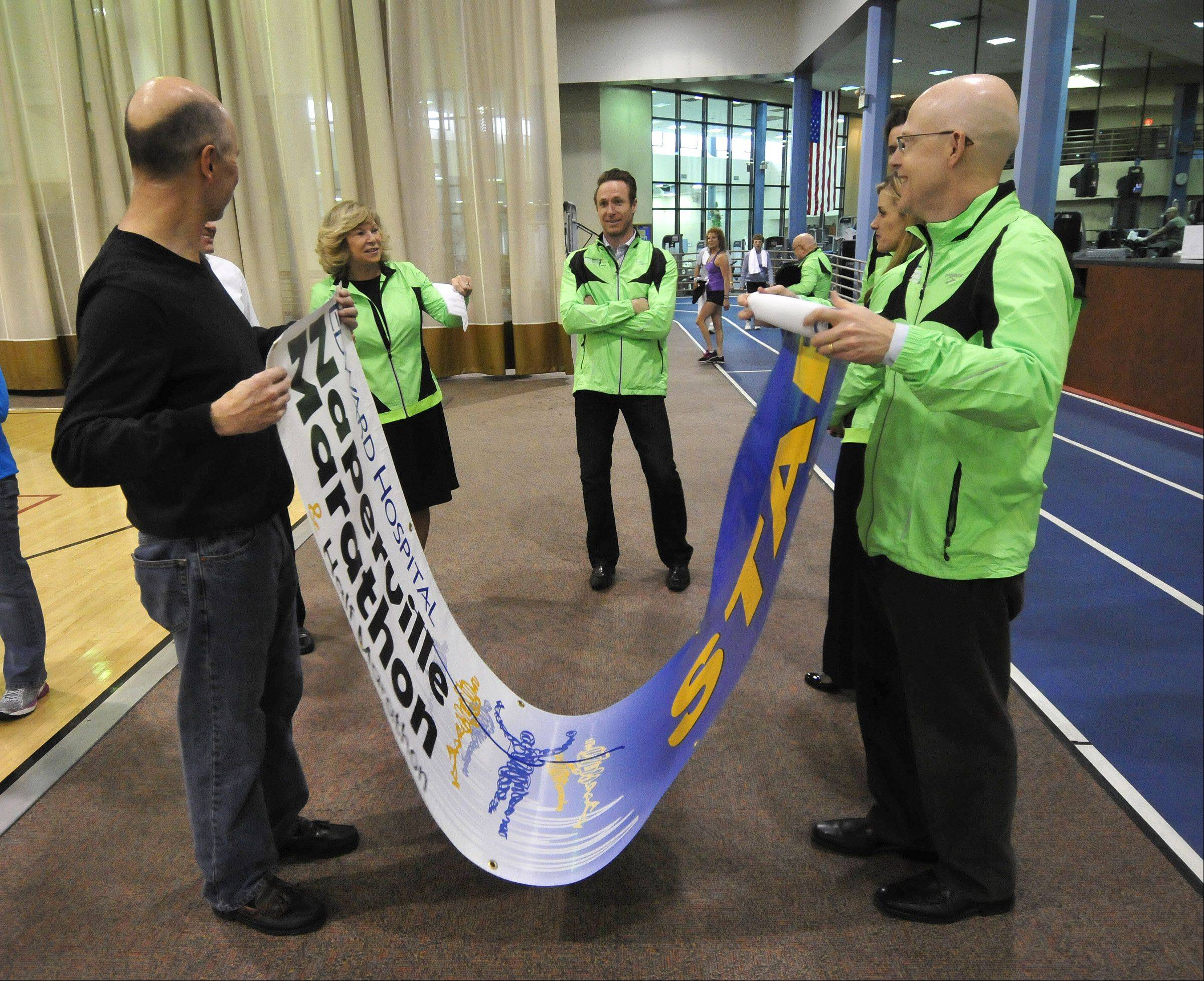 Edward Hospital President & CEO Pam Davis, second from left, comments on the banner that will be placed at the start of Naperville's inaugural marathon this fall.