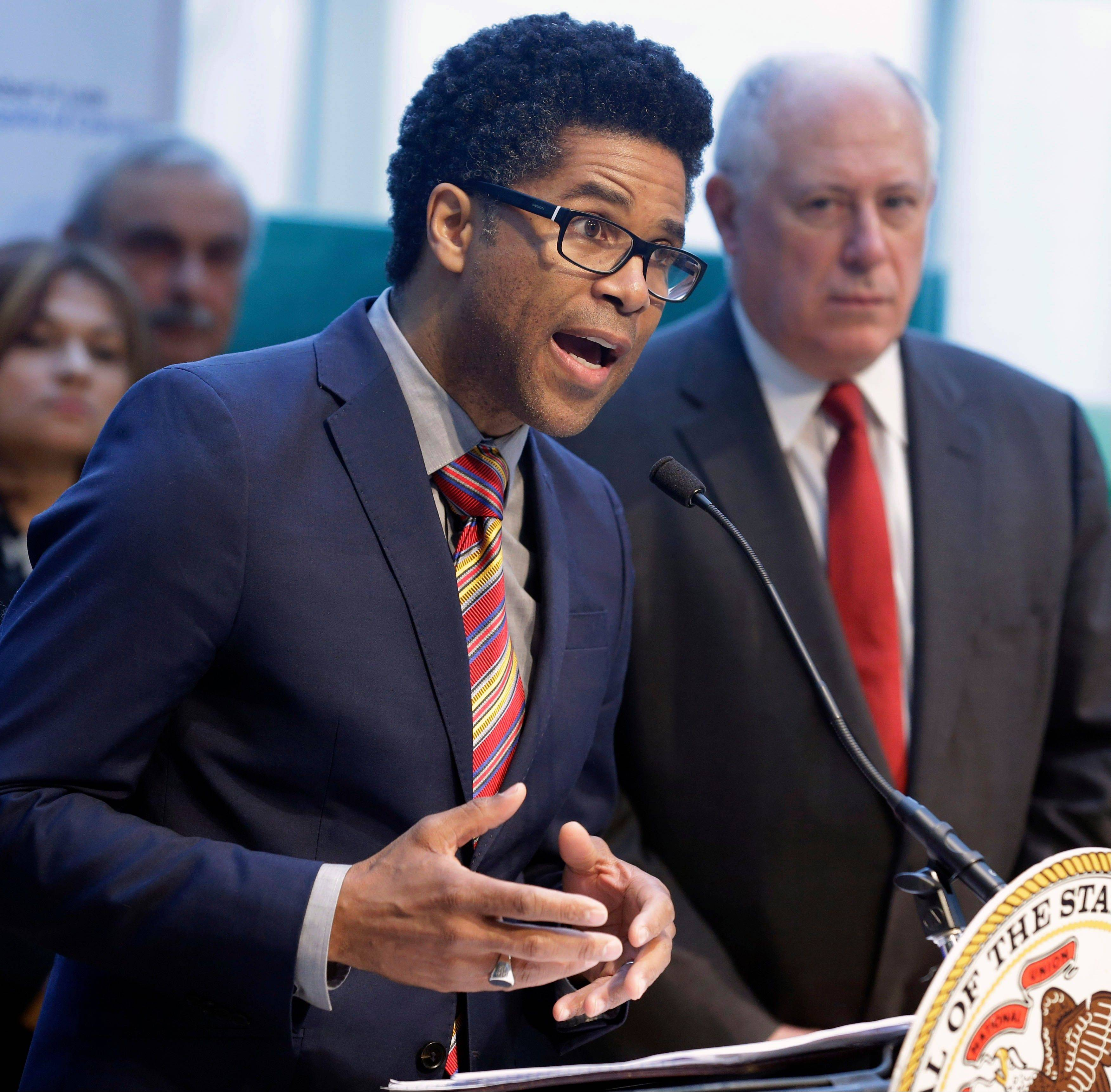Illinois Department of Public Health Director LaMar Hasbrouck, left, accompanied by Gov. Pat Quinn, speaks at a news conference on youth violence Monday in Chicago.