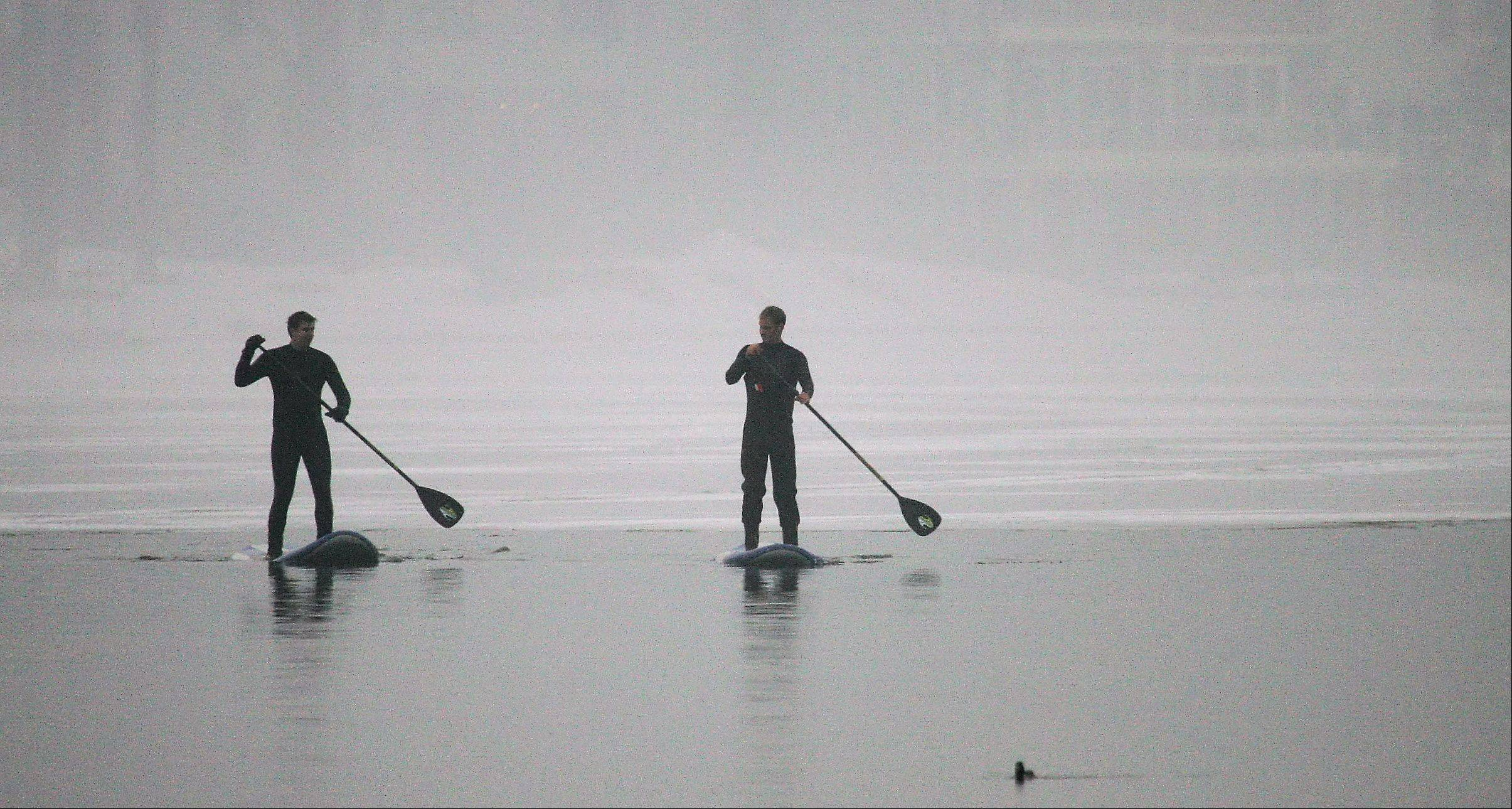 Two water enthusiasts take to the open sections of water on stand up paddle boards as they navigate around the ice on Diamond Lake in Mundelein. Fog surrounded them as they wore wetsuits to go from one ice island to the next.