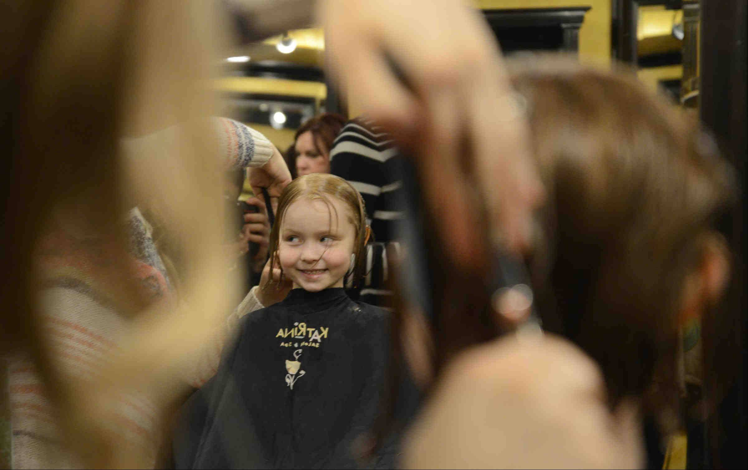 Sienna Biwer, 5, has her long hair cut by stylist Kelly Shremp Sunday at Katrina Salon and Spa in Batavia during the Save The Date, Save Your Hair Cancer Community Awareness event. Anyone donating eight inches of hair received a free haircut. The locks will be donated to organizations to make wigs for cancer patients.