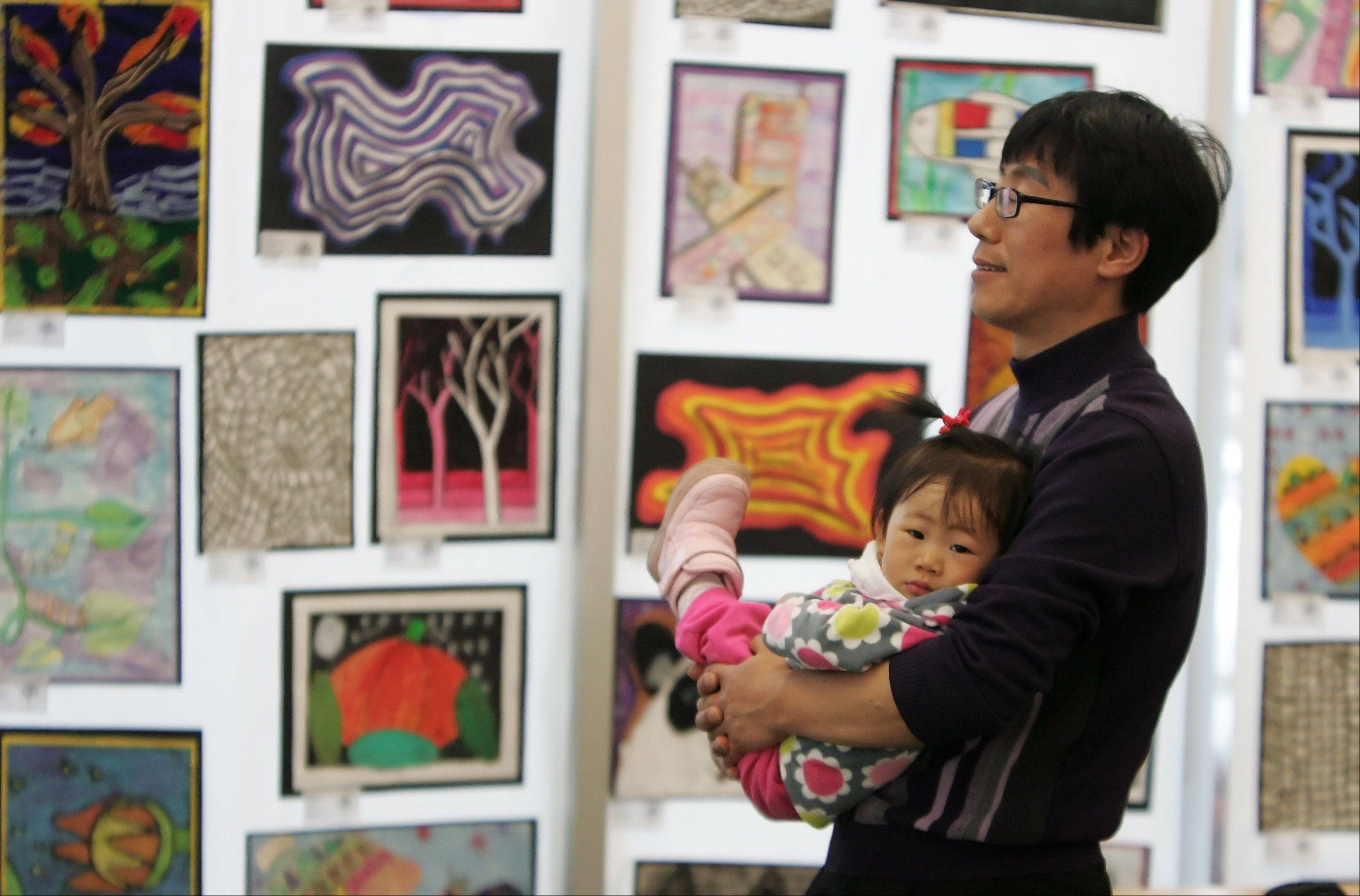 Daniel Choe, of Vernon Hills, holds his daughter, Yehee, as he looks at artwork by students from Townline School during the Hawthorn School District 73 Third Annual Youth Art Show on display at the Aspen Drive Library in Vernon Hills. The show will be up through April 1.