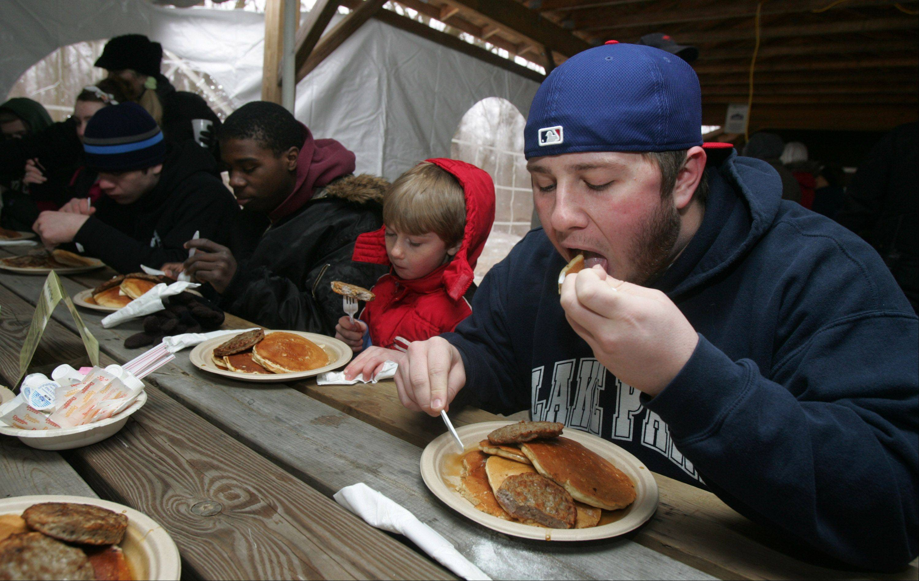 Cole Sheeks, 19, right, Landon Sheeks, 7, and Delvon Moneyham, 19, eat pancakes during the 29th Annual Sugar Bush Fair Sunday at the Spring Valley Nature Center in Schaumburg. The event featured a pancake breakfast with maple syrup, demonstrations of maple syrup production and hayrides.