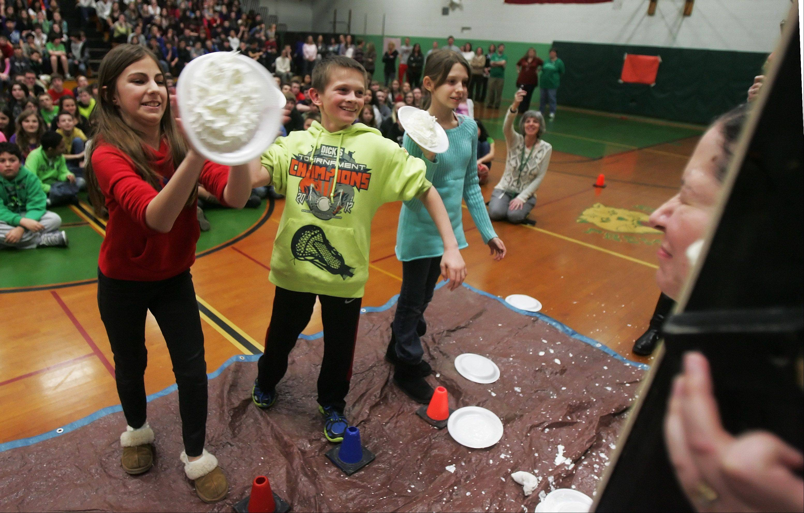 Students Samantha Faruzzi, left, Eli Daugs, and Amanda Valenti, throw pies at thier math teachers at Fremont Middle School in Mundelein Thursday as part of a Pi Day fundraiser for St. Jude Children's Research Hospital. Pi is 3.14, Thursday was March 14, and students donated $3.14 to enter a raffle to throw a pie at their favorite math teacher.