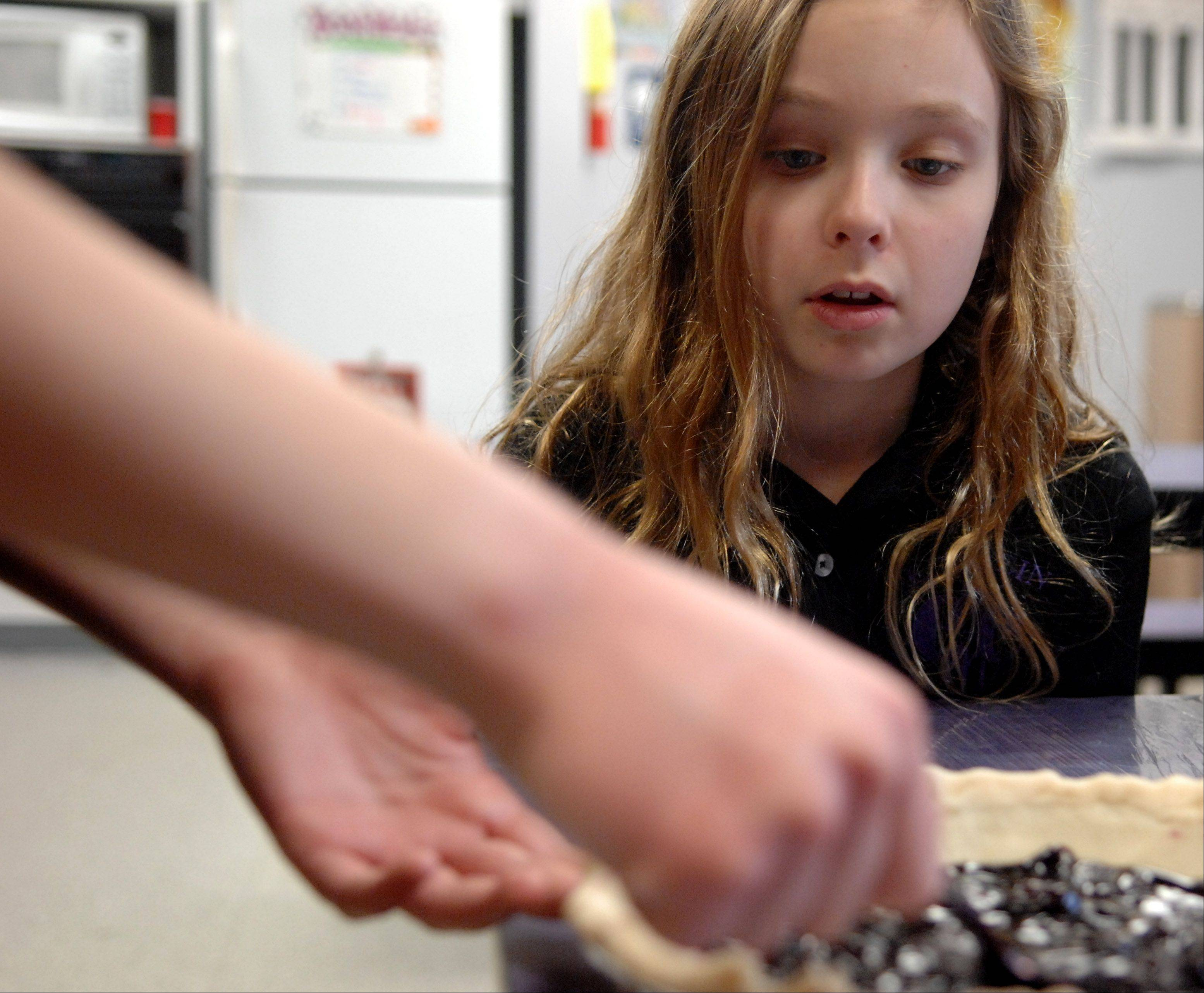 4th-grader Emily Goldenberg of Streamwood watches while another student stirs blueberry filling as they make pies for Pi day at Einstein Academy in Elgin Thursday. They're taking them to the residents at Rosewood Care Center in Elgin on Friday.