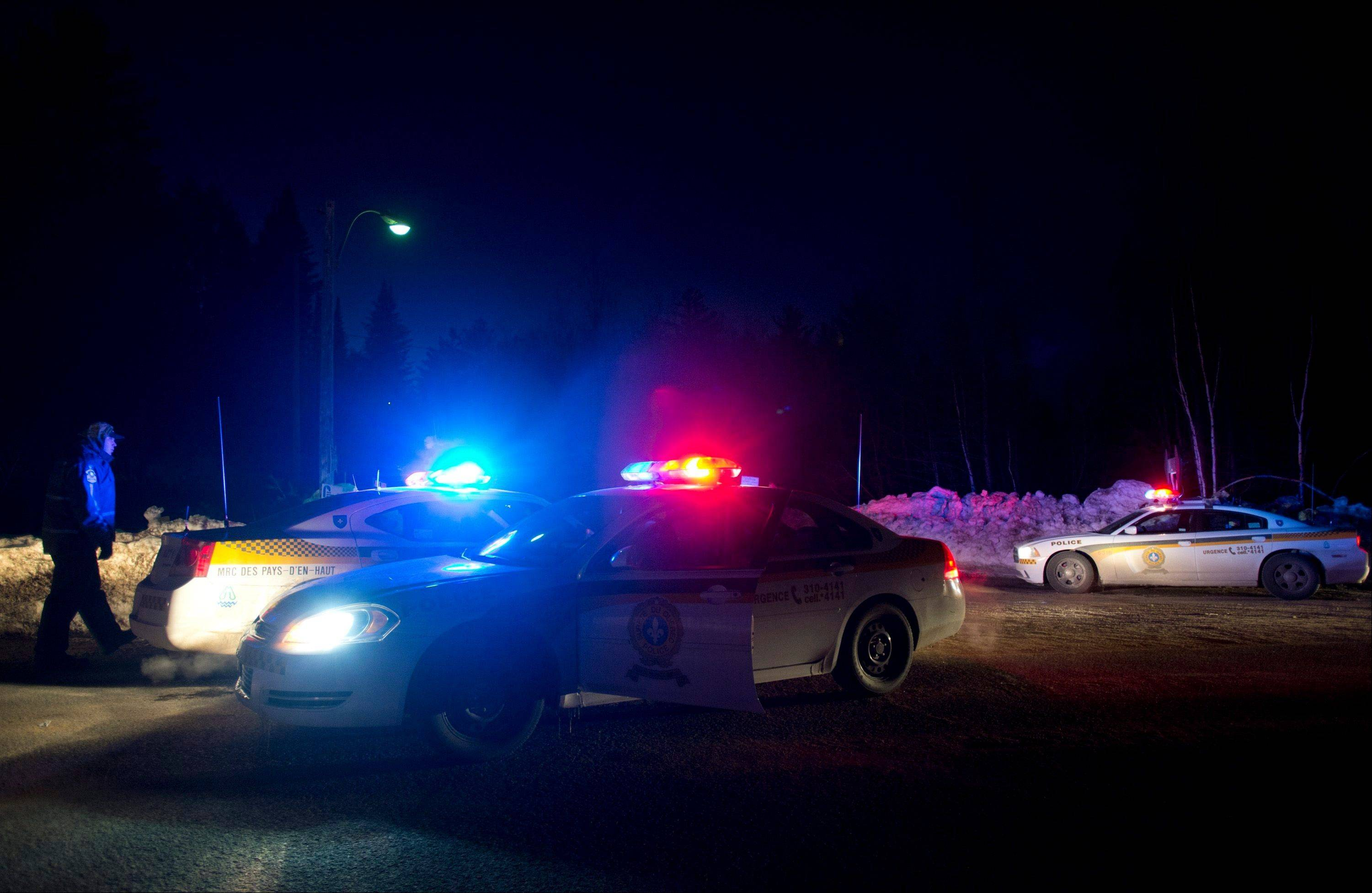 Police vehicles block a road just outside the town of Chertsey, Quebec, Sunday, during a search for escaped prisoners. A dramatic daylight jailbreak involving two Quebec inmates climbing a rope into a hovering helicopter swiftly escalated into a large police operation Sunday night in which at least one escapee was tracked down hours after he fled.