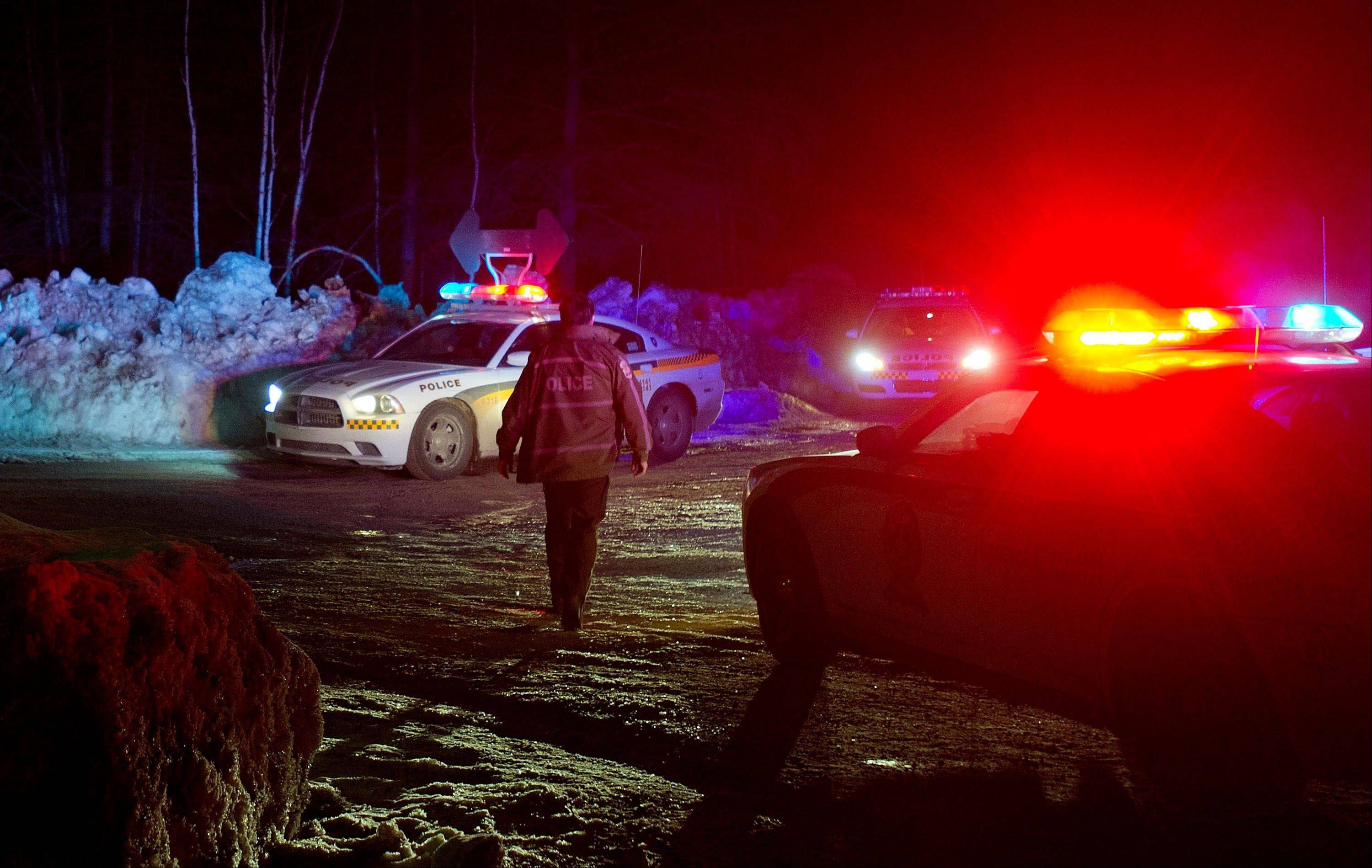 Police vehicles block a road just outside the town of Chertsey, Quebec, Sunday during a search for escaped prisoners.