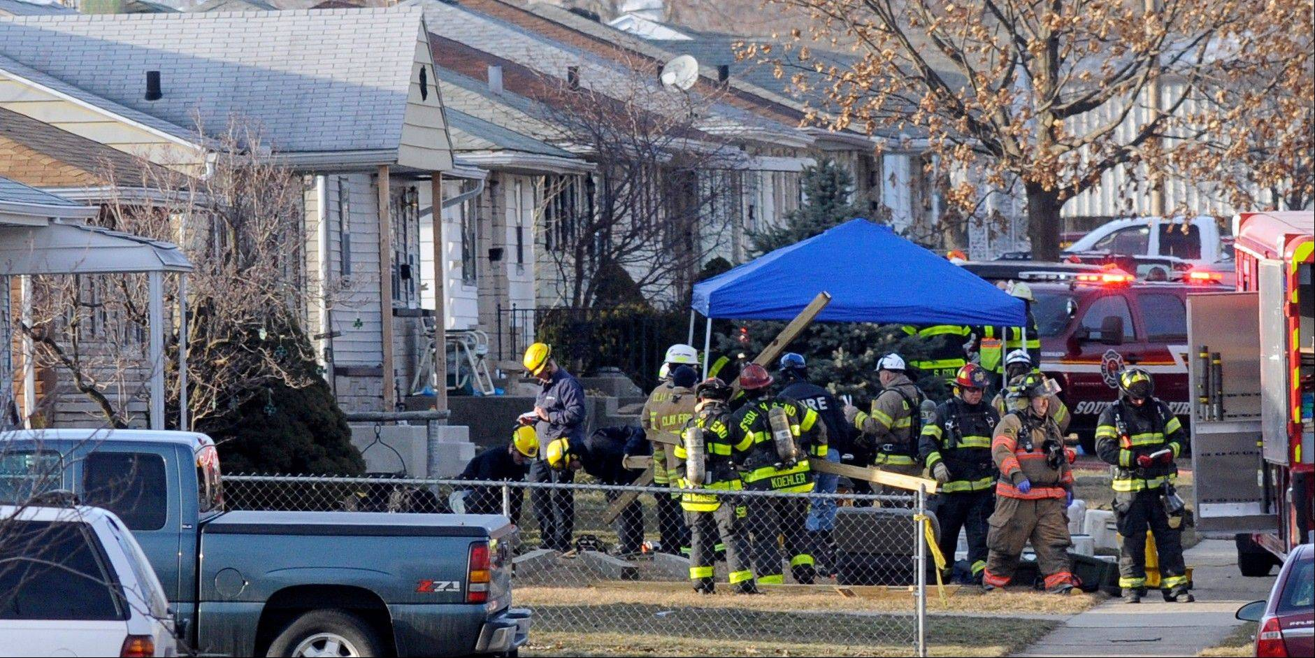 South Bend police and fire officials examine a home where a plane crash occurred near the South Bend Regional Airport Sunday in South Bend, Ind.