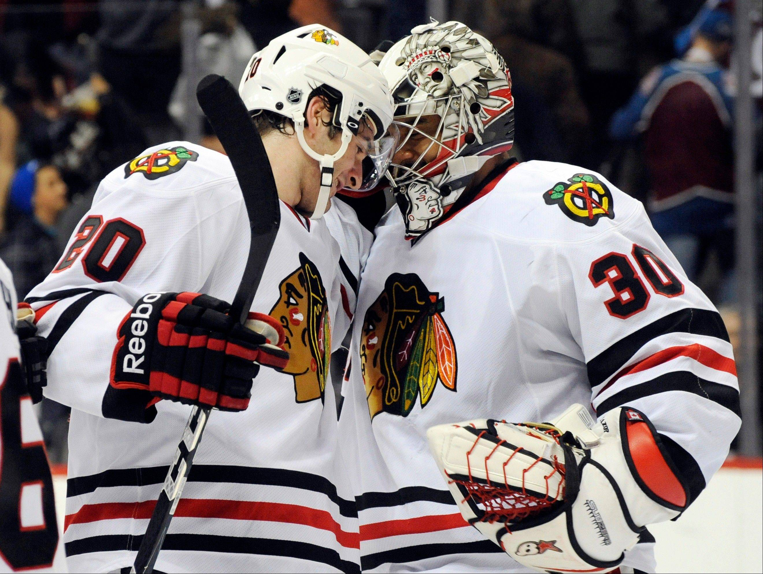 Blackhawks goalie Ray Emery celebrates with Brandon Saad during Monday night's victory.