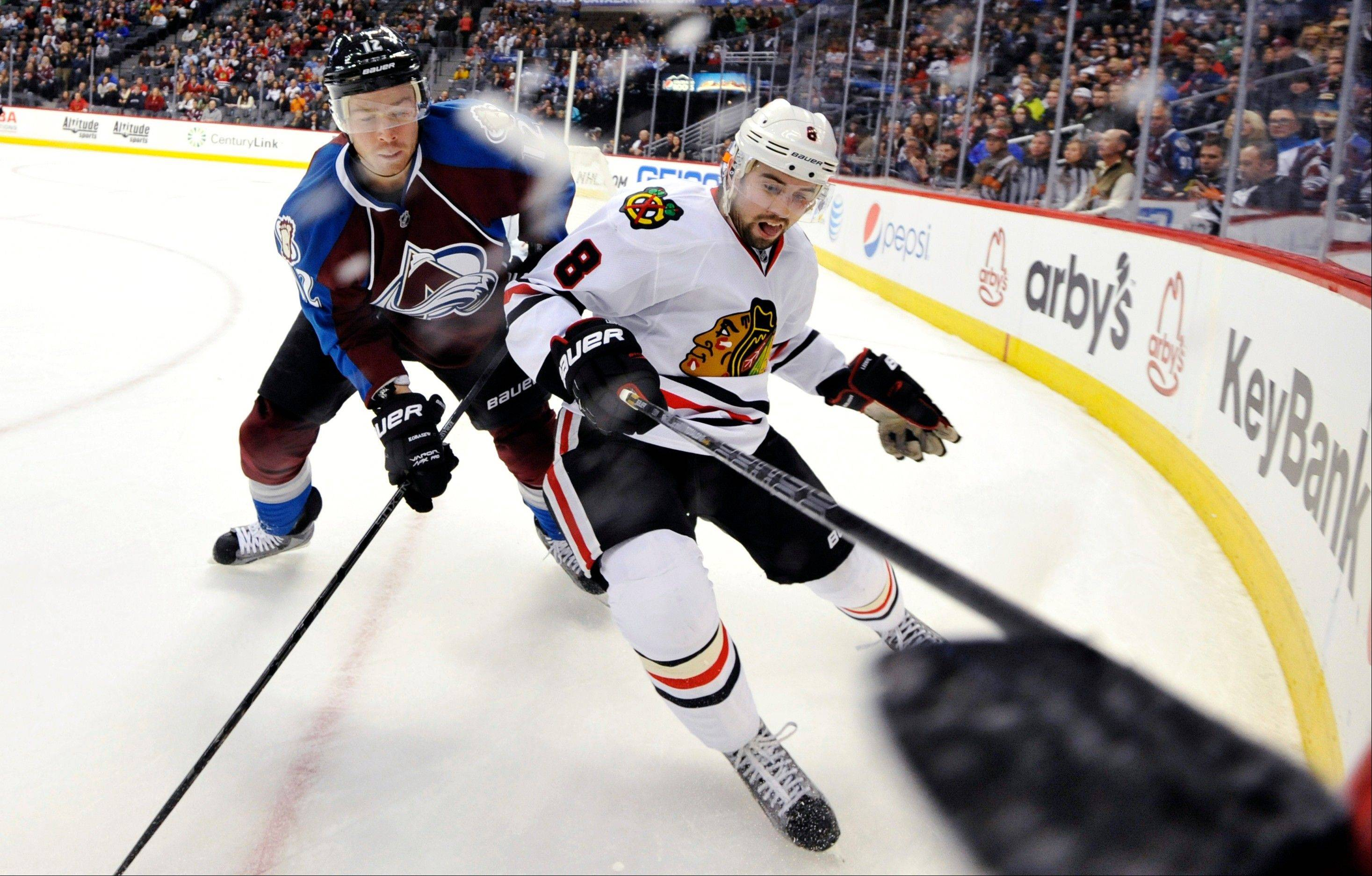 Colorado Avalanche right wing Chuck Kobasew (12) and Chicago Blackhawks defenseman Nick Leddy (8) chase a puck into the corner during the third period of an NHL hockey game, Monday, March 18, 2013, in Denver. Chicago won 5-2.
