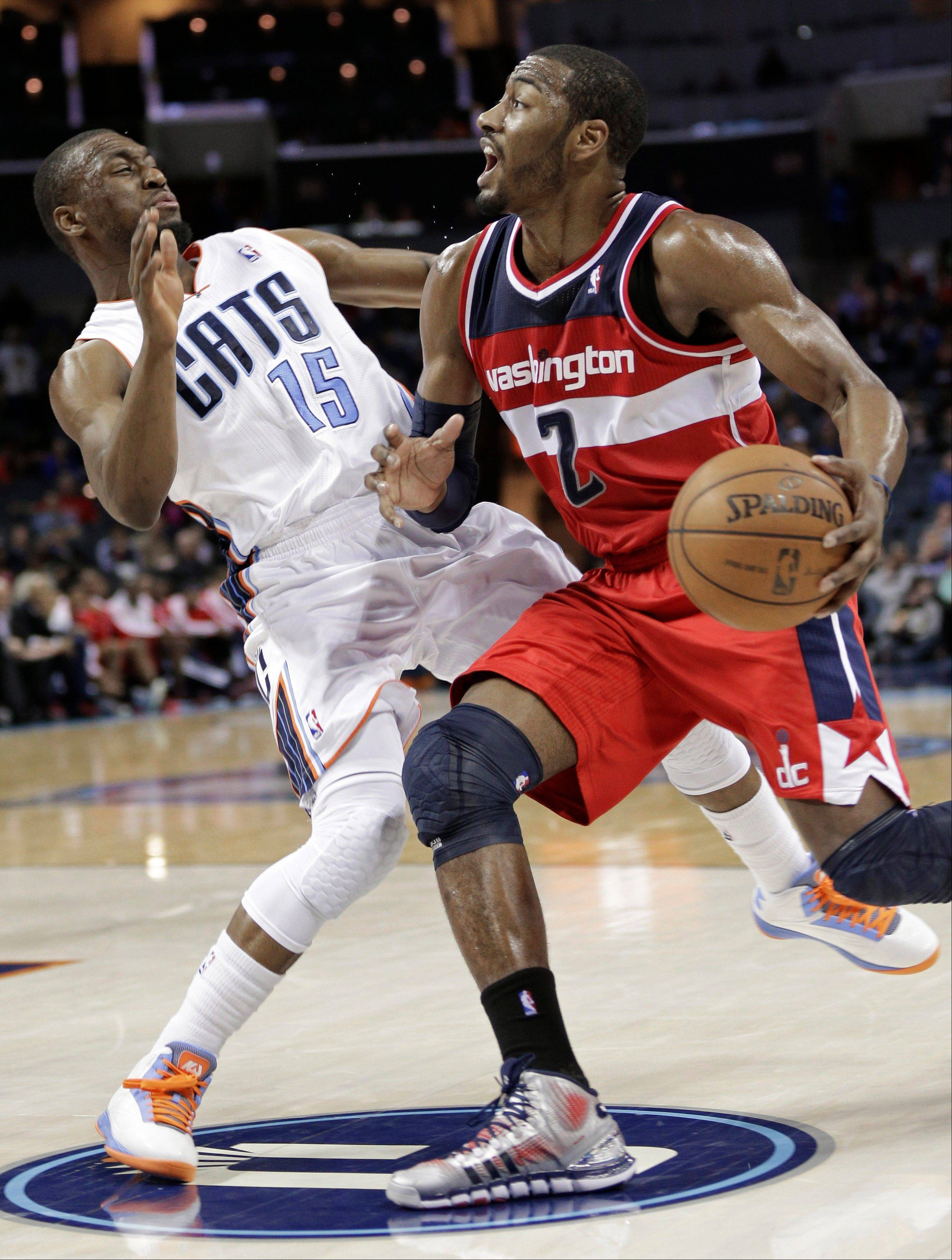 Washington Wizards' John Wall (2) knocks down Charlotte Bobcats' Kemba Walker (15) during the second half of an NBA basketball game in Charlotte, N.C., Monday, March 18, 2013. Wall was called for a charging foul on the play. The Bobcats won 119-114.