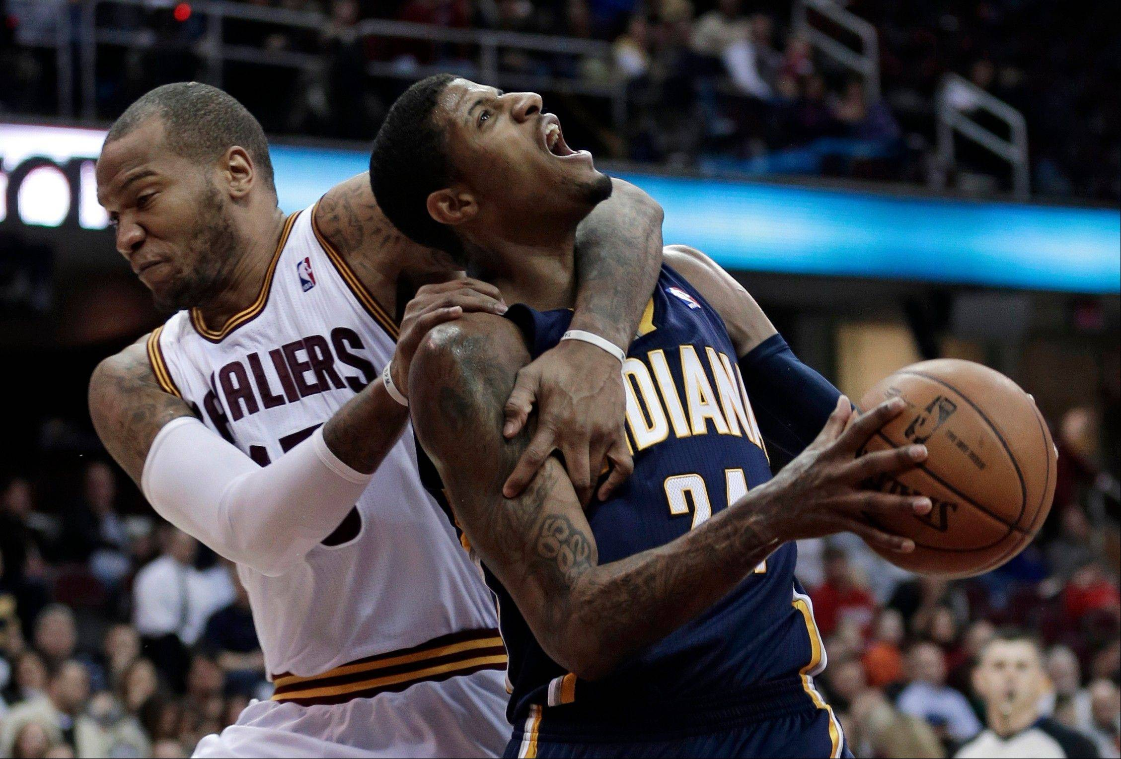 Cleveland Cavalier's Marreese Speights, left, fouls Indiana Pacers' Paul George during the third quarter of an NBA basketball game Monday in Cleveland. Speights was ejected for a flagrant foul. The Pacers won 111-90.