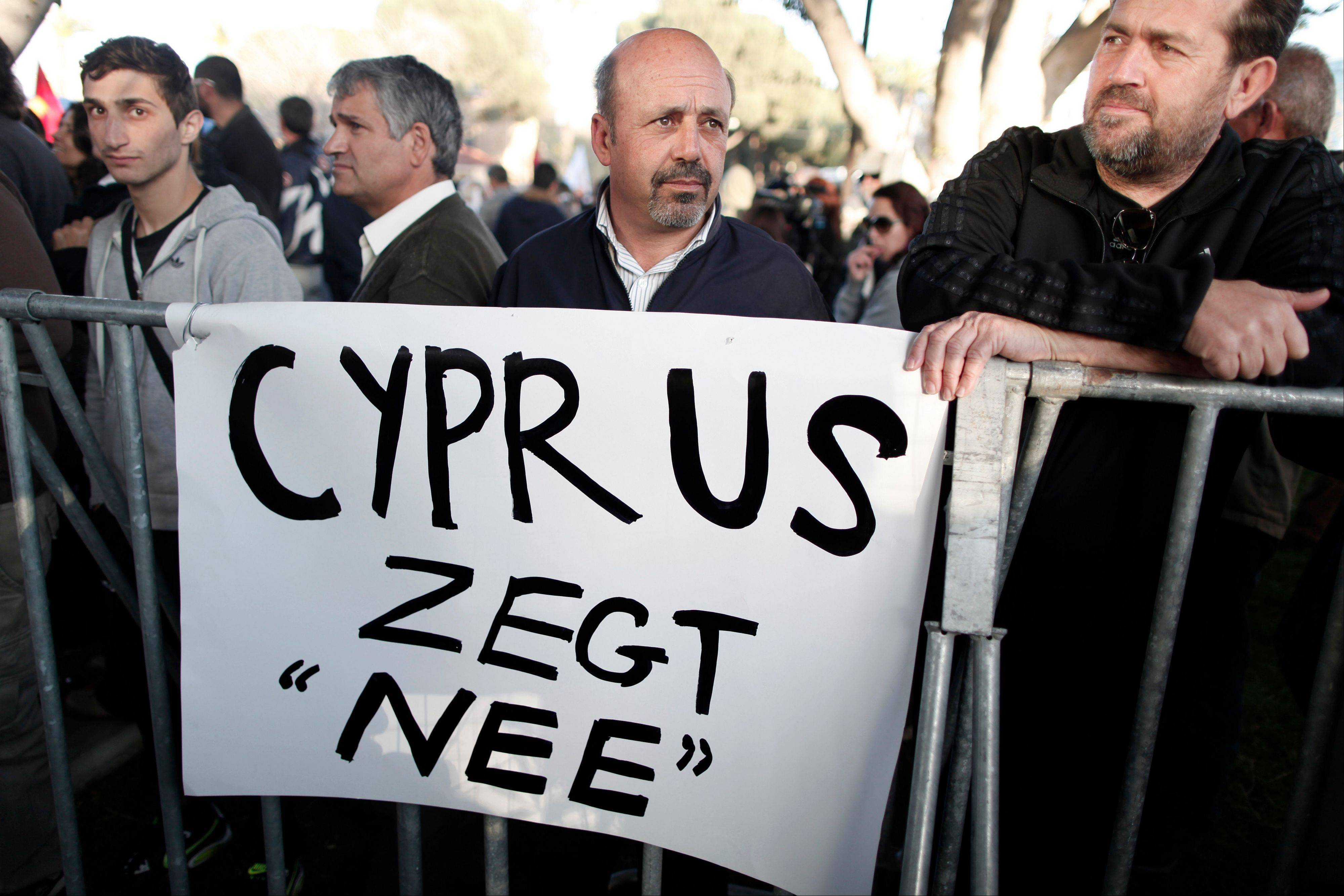 Protesters stand in front of a banner which reads �Cyprus Says No� during a crucial parliamentary vote on a plan to seize a part of depositors� bank savings in central Nicosia Tuesday.