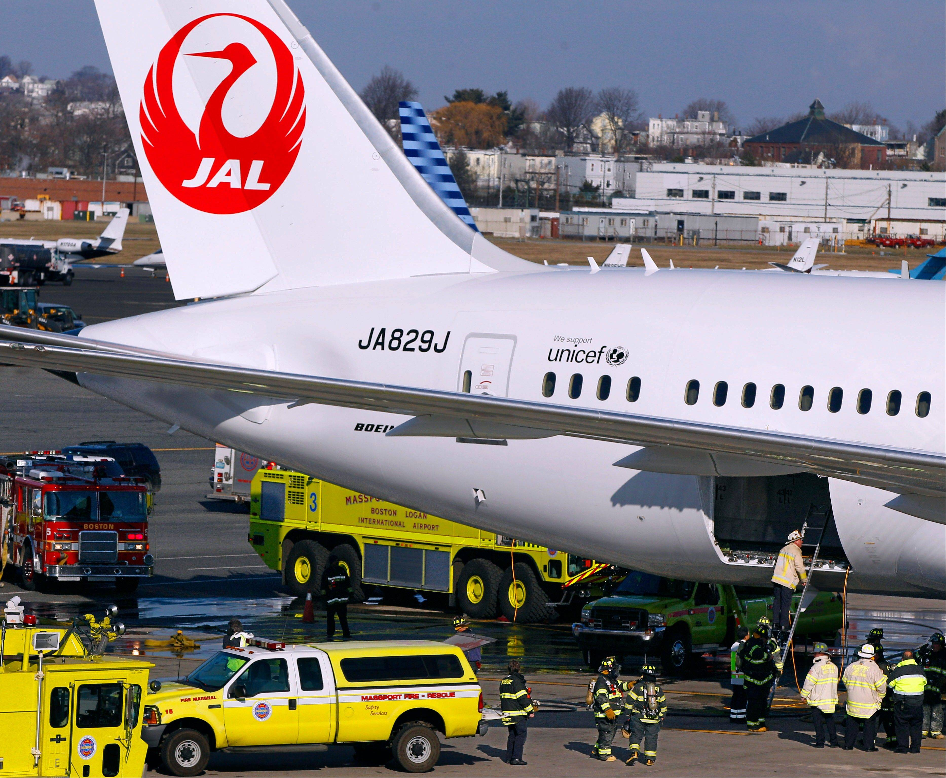 A Japan Airlines Boeing 787 jet aircraft is surrounded in early January by emergency vehicles while parked at a terminal E gate at Logan International Airport in Boston as a fire chief looks into the cargo hold.