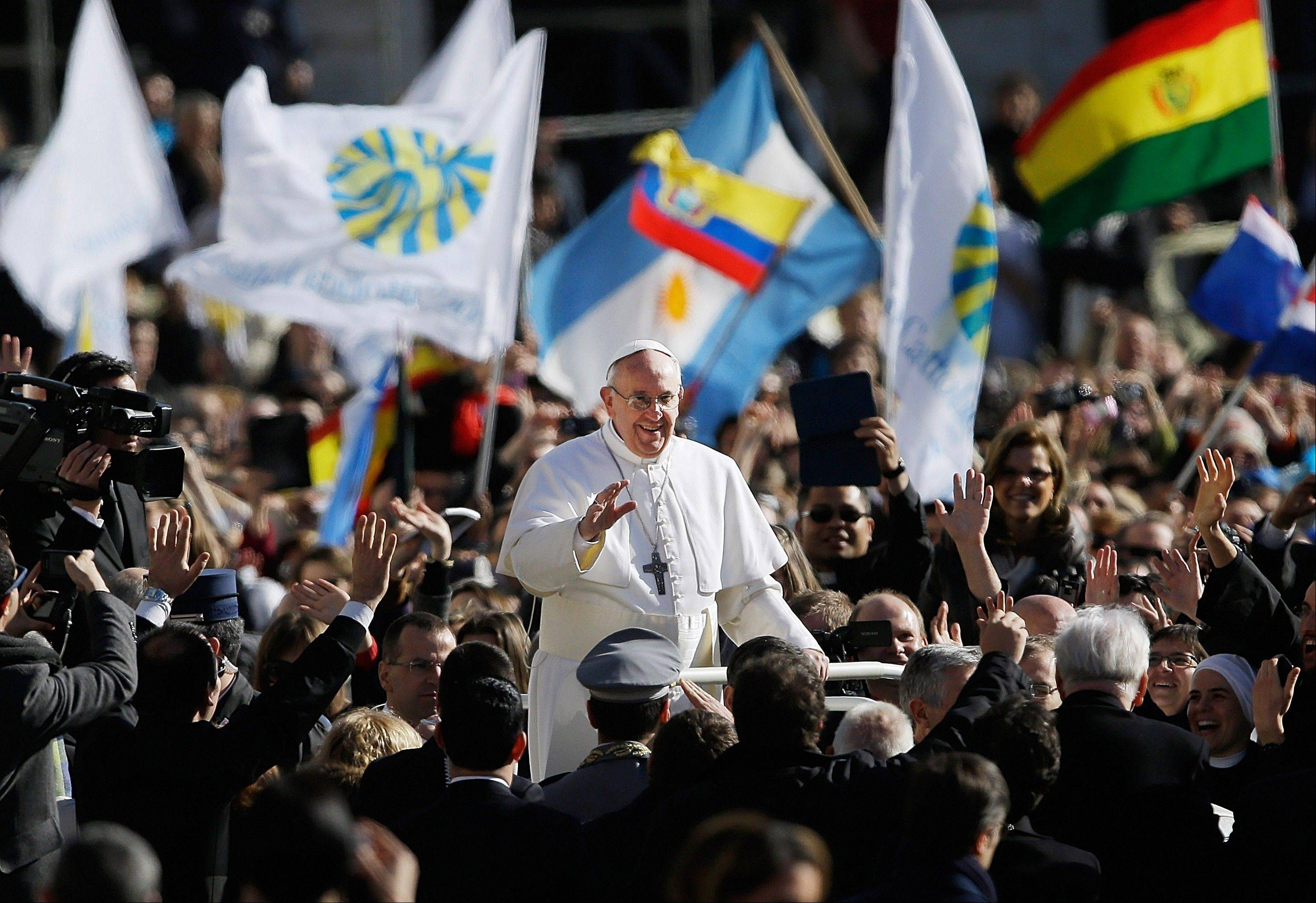 Pope Francis waves to crowds as he arrives to his inauguration Mass in St. Peter�s Square at the Vatican, Tuesday