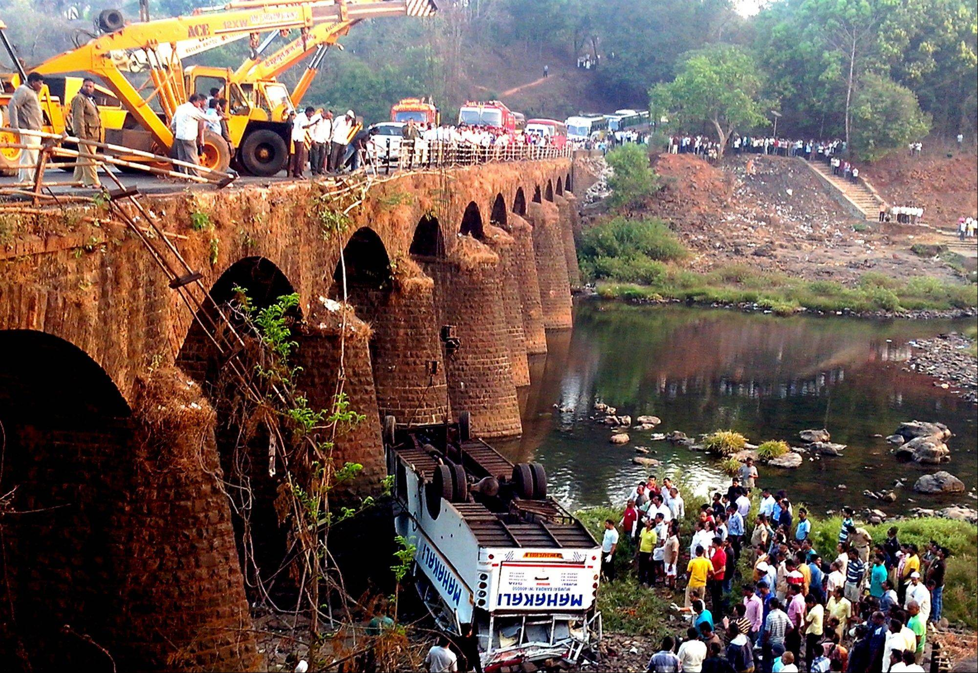 Rescuers and others gather at the site of a bus accident in Ratnagiri district, in the western Indian state of Maharashtra, Tuesday. The bus packed with passengers crashed through a guard rail and fell off a bridge, killing at least 37 people and injuring another 15, police said.