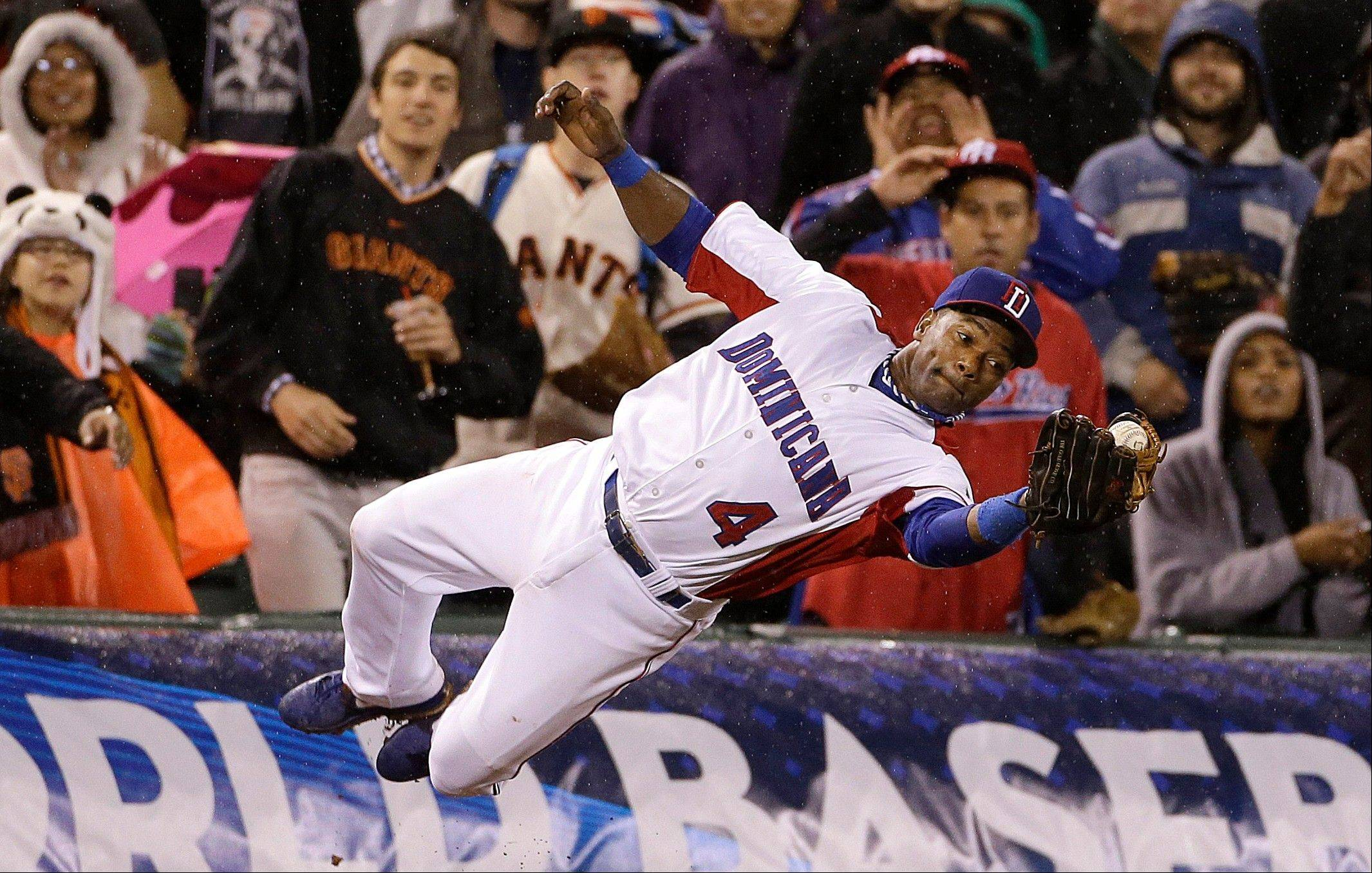 The Dominican Republic's Miguel Tejada (4) catches a foul ball hit by Puerto Rico's Jesus Feliciano during the seventh inning of the championship game of the World Baseball Classic in San Francisco, Tuesday, March 19, 2013. (AP Photo/Eric Risberg)