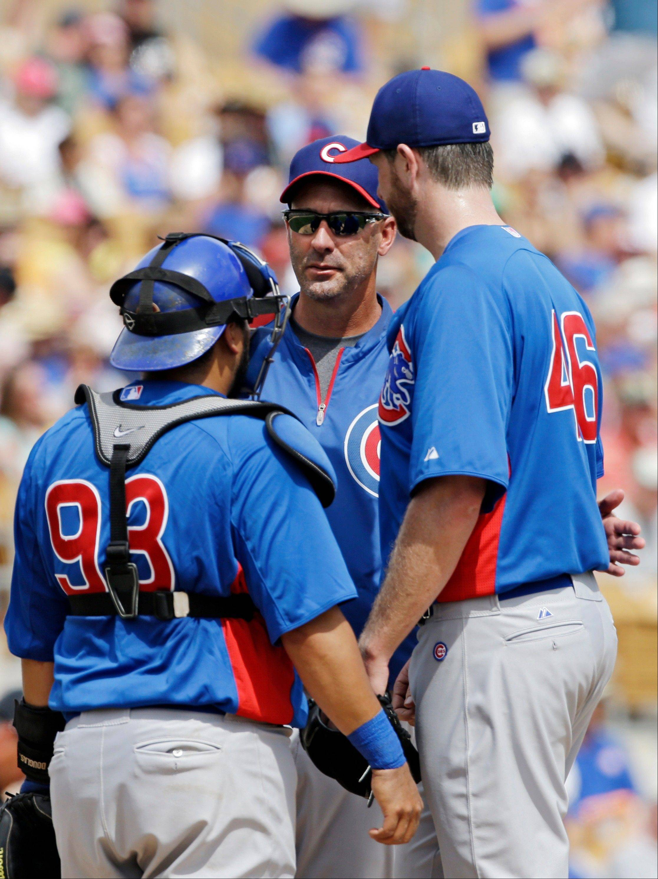 Chicago Cubs manager Dale Sveum, center, takes starting pitcher Scott Feldman out of an exhibition spring training baseball game against the Chicago White Sox in th fourth inning Friday, March 15, 2013, in Glendale, Ariz. Cubs catcher Dioner Navarro (93) listens in. (AP Photo/Mark Duncan)