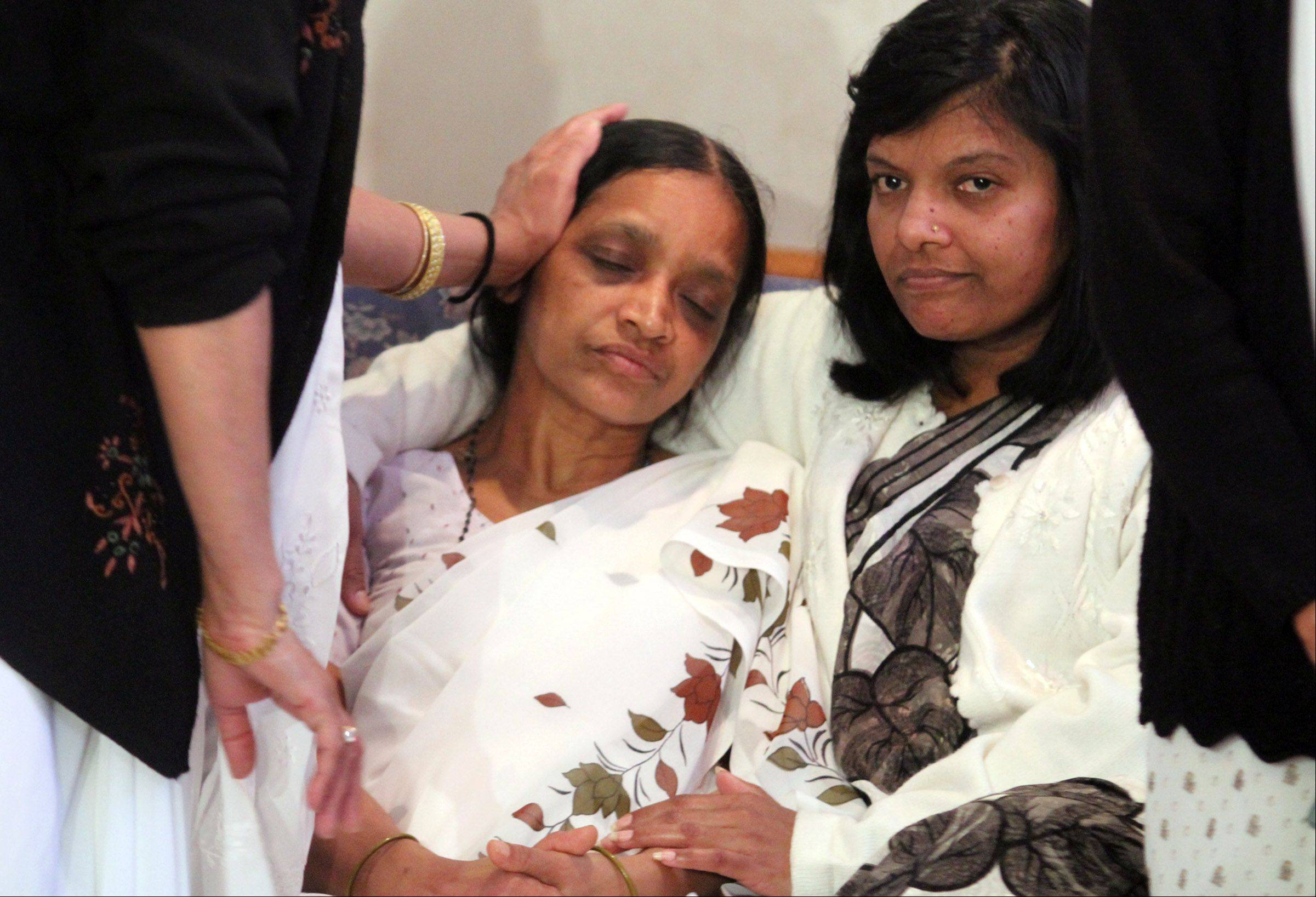 Anandkumar Jaiswal's mother, Malti Jaiswal, is consoled by family members Tuesday as Streamwood police announce an increase in the reward for information that may help find the person behind his murder Saturday during a robbery.