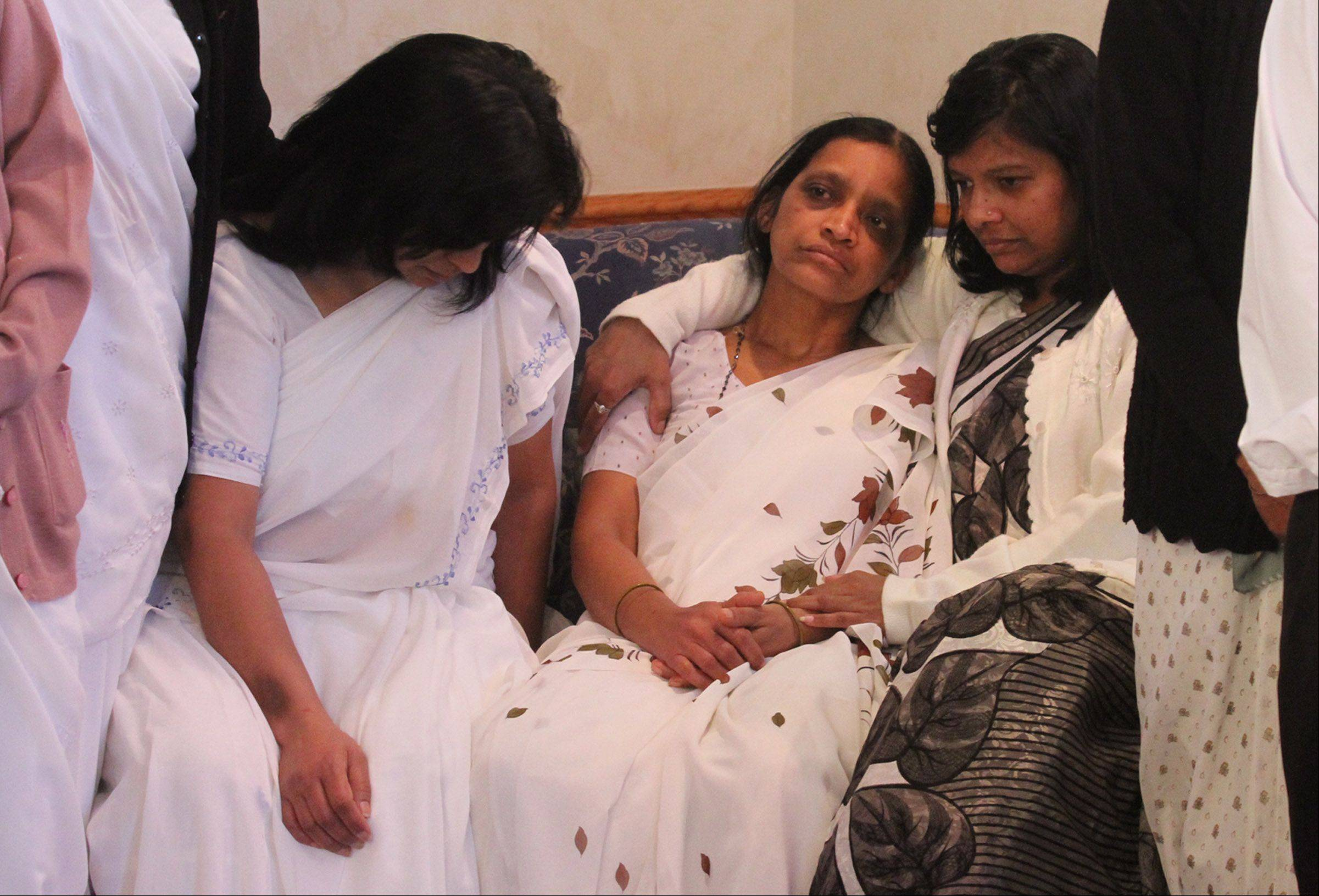 Anandkumar Jaiswal's mother, Malti Jaiswal, is consoled by family members as Streamwood police announce an increase in the reward for information that may help find the person behind his murder Saturday during a robbery.