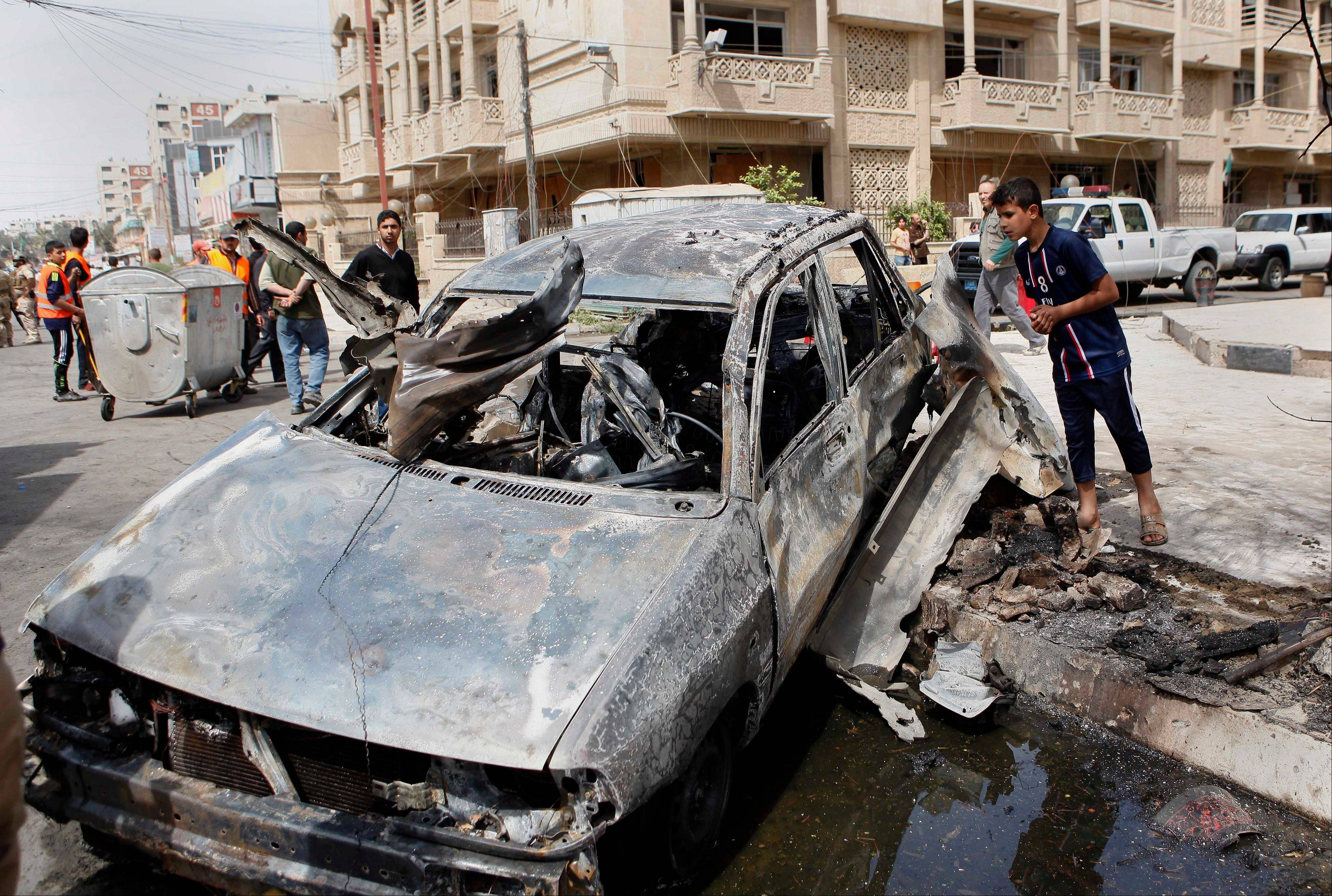 People inspect a car destroyed in a car bomb attack close to one of the main gates to the heavily-fortified Green Zone, which houses major government offices and the embassies of several countries, including the United States and Britain in Baghdad on Tuesday.