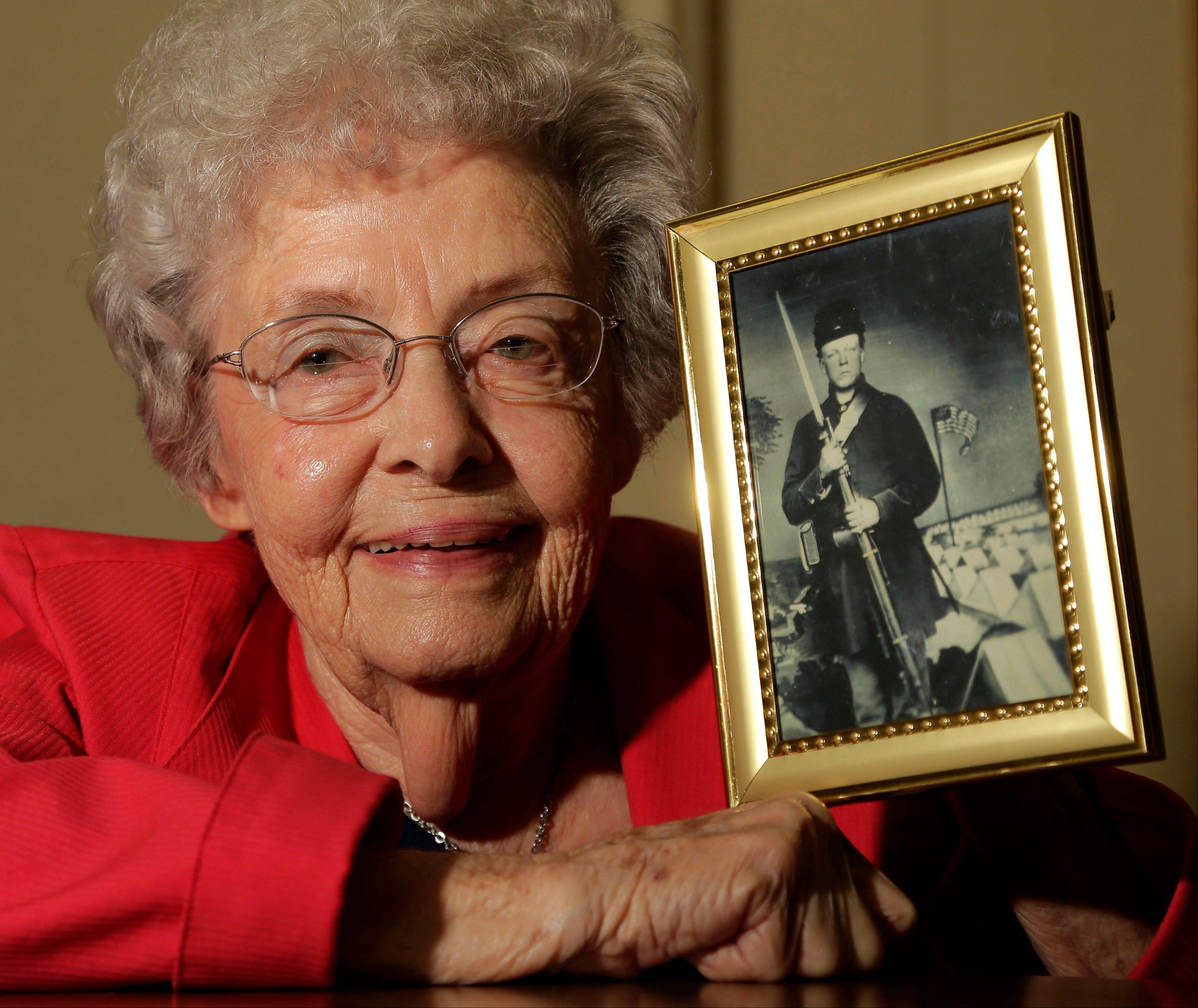 Juanita Tudor Lowrey, 86, poses with a photo of her father, Civil War veteran Hugh Tudor on Tuesday in Kearney, Mo. Lowrey received pension benefits related to her father's Civil War service until she was 18 after her father died when she was 2 years old.