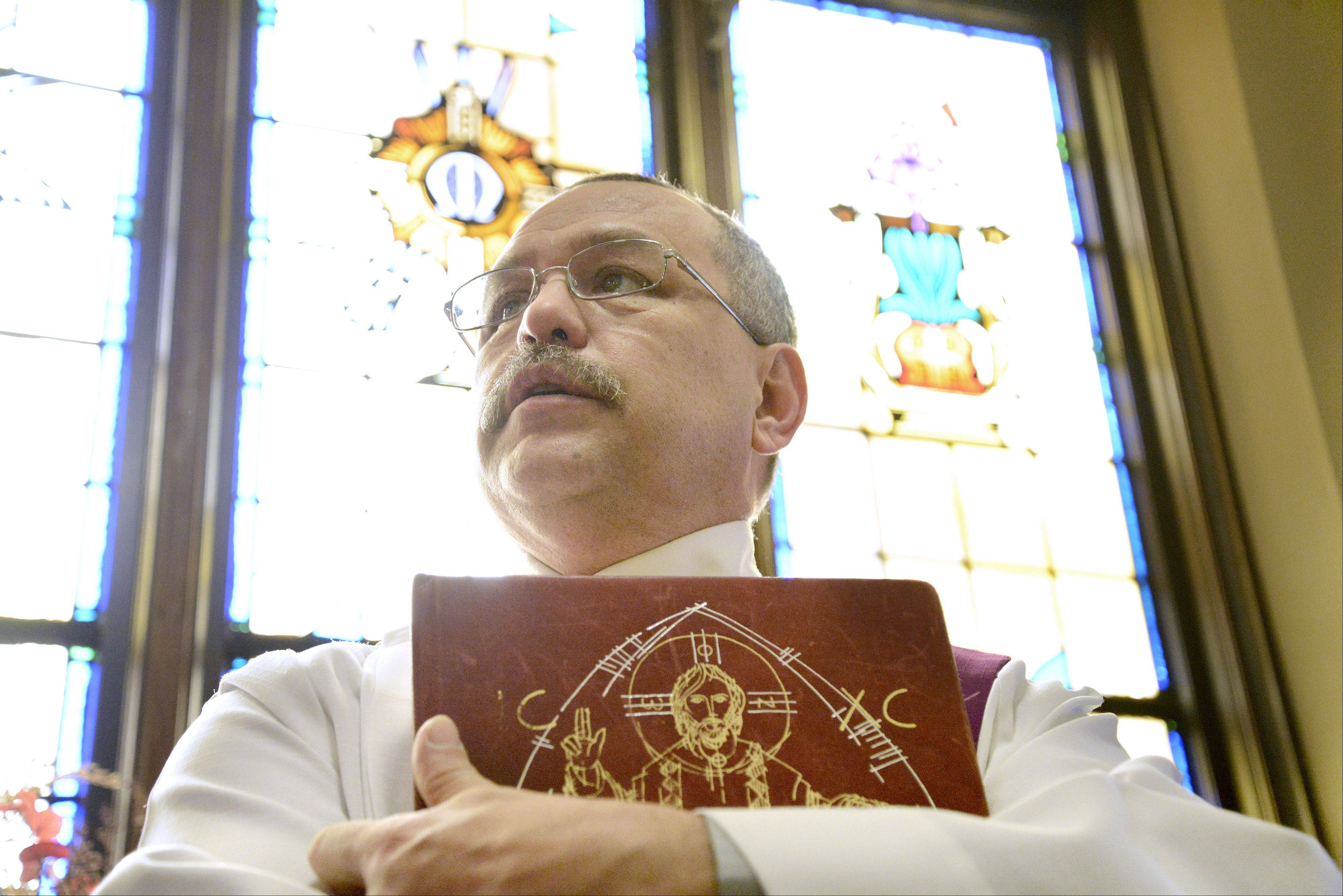 Deacon Luis Saltigerald talks about Pope Francis before a Spanish service starts at St. Mary's Church in West Chicago on Sunday. The parish's large Latino population is excited about the new pope's Latin American background.