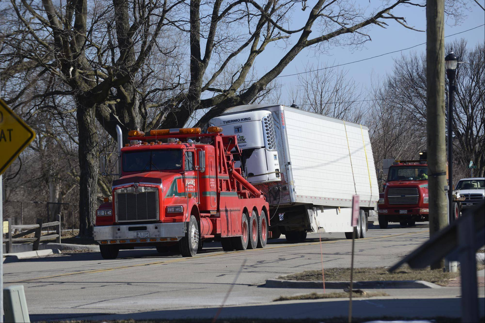 A cheese truck trailer involved in an early morning crash at Reinking Road and Route 20 in Pingree Grove is hauled away from the scene near Marshall Road.