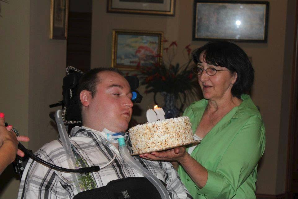 Celebrating his 30th and last birthday last summer, Rob Komosa gets a cake from his mother, Barbara Komosa.