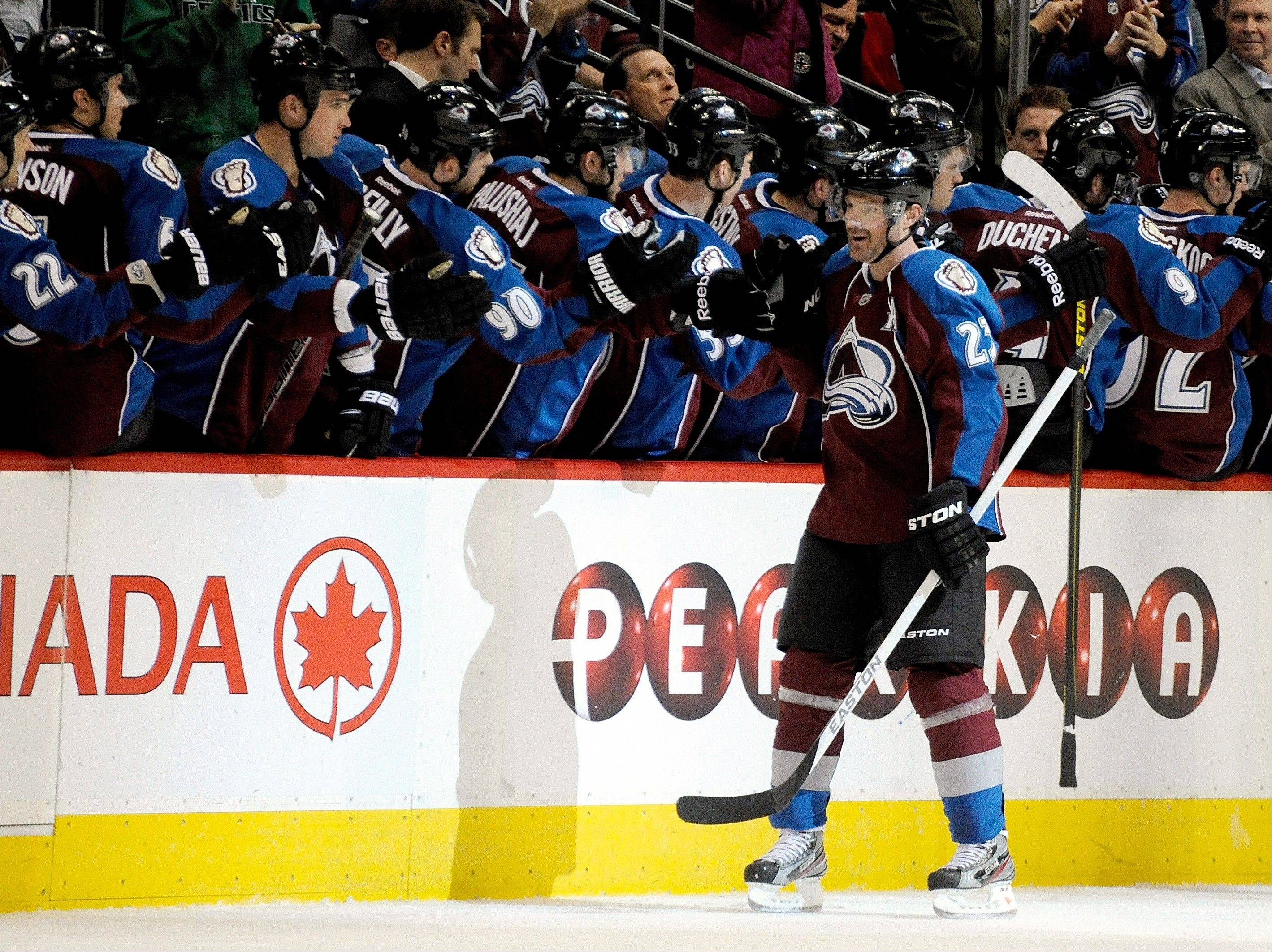 Colorado Avalanche right wing Milan Hejduk (23), celebrates a goal against the Chicago Blackhawks with teammates during the second period .