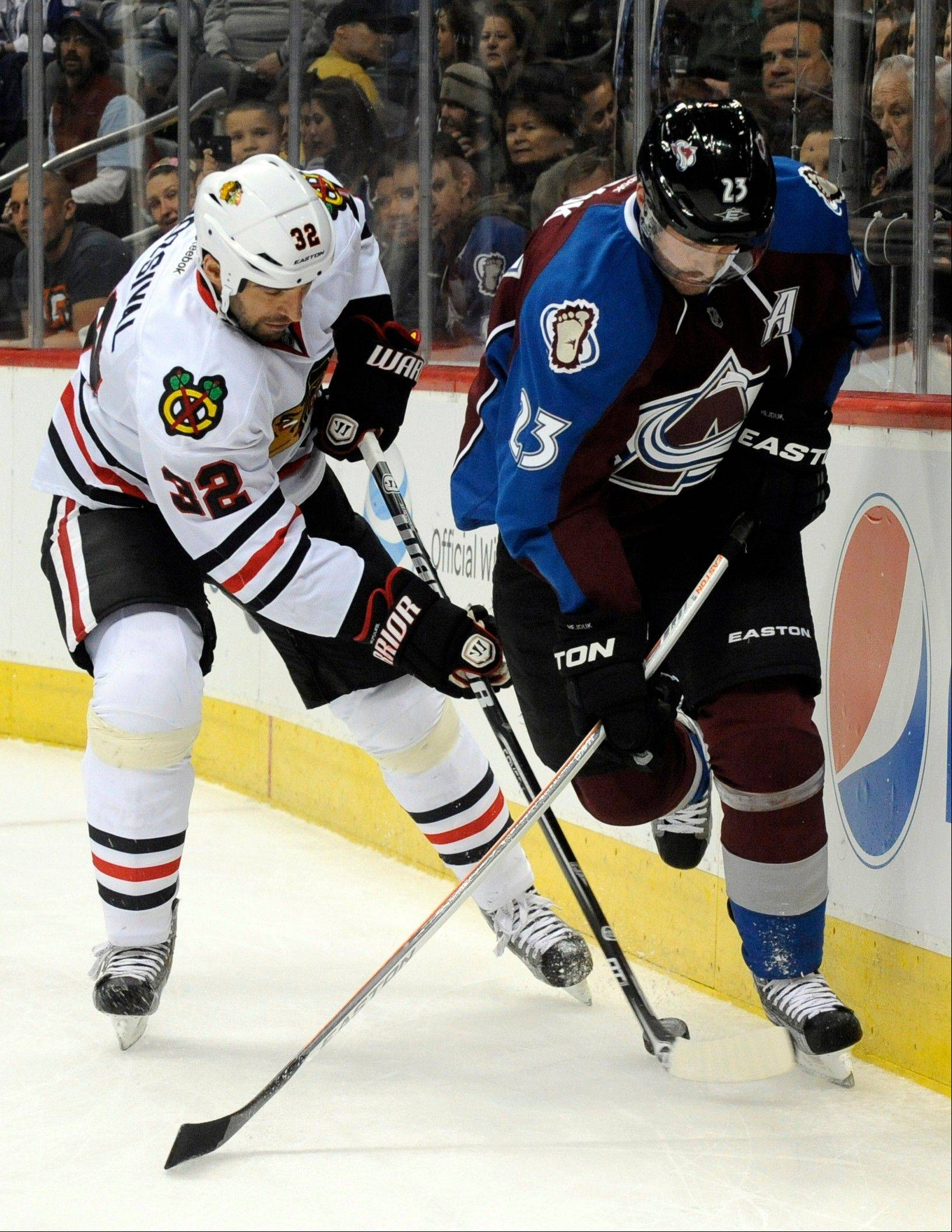 Chicago Blackhawks defenseman Michal Rozsival (32), and Colorado Avalanche right wing Milan Hejduk (23), chase the puck into the corner during the first period.