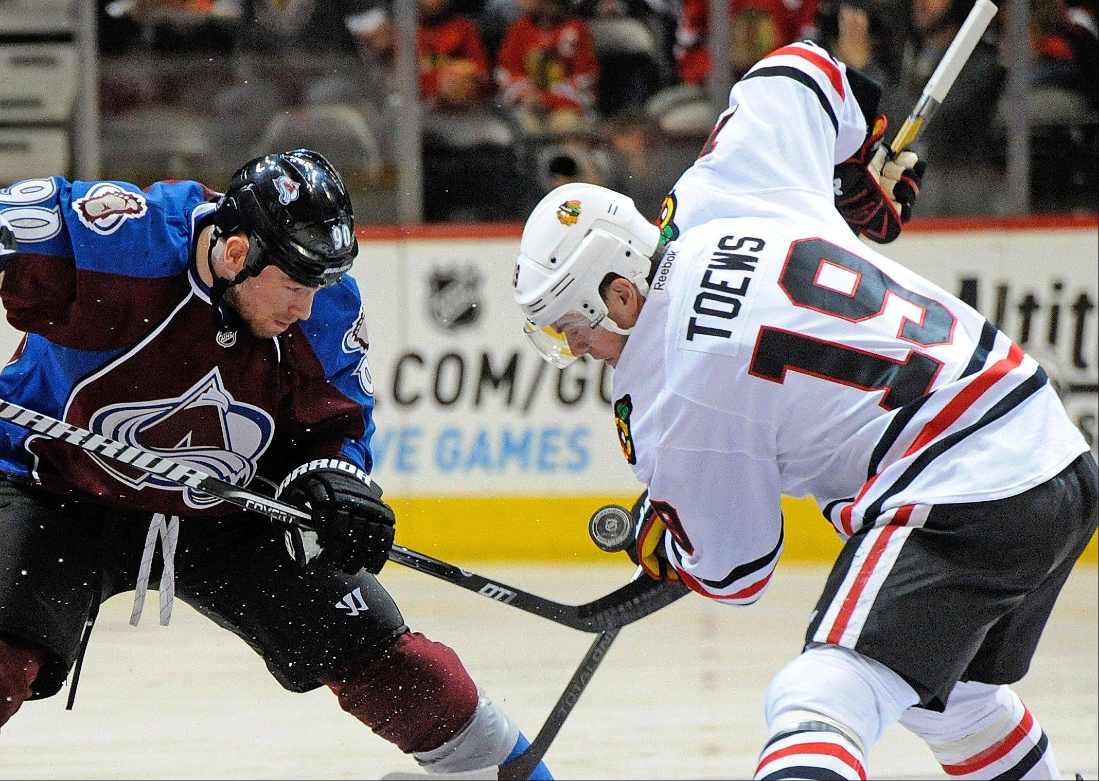 Colorado Avalanche center Ryan O'Reilly (90) and Chicago Blackhawks center Jonathan Toews (19) fight for the puck during the first period.